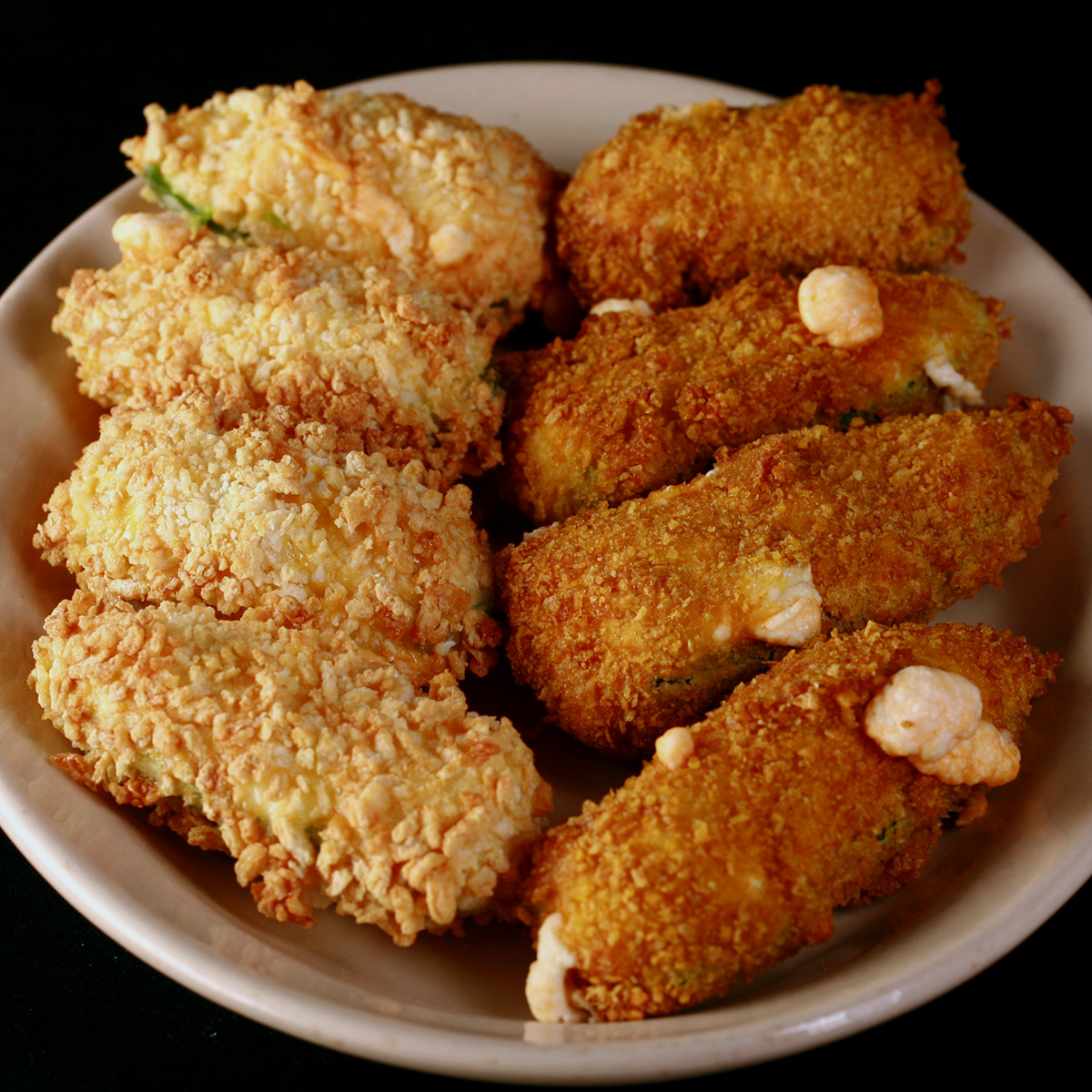 A small ivory colour plate holds two different types of gluten-free jalapeno poppers