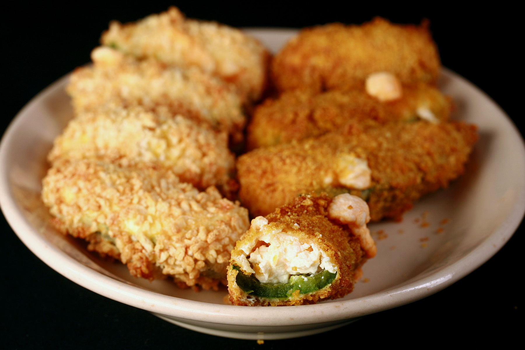 A close up view of air fryer gluten-free jalapeno poppers. One has a bite taken out of it.
