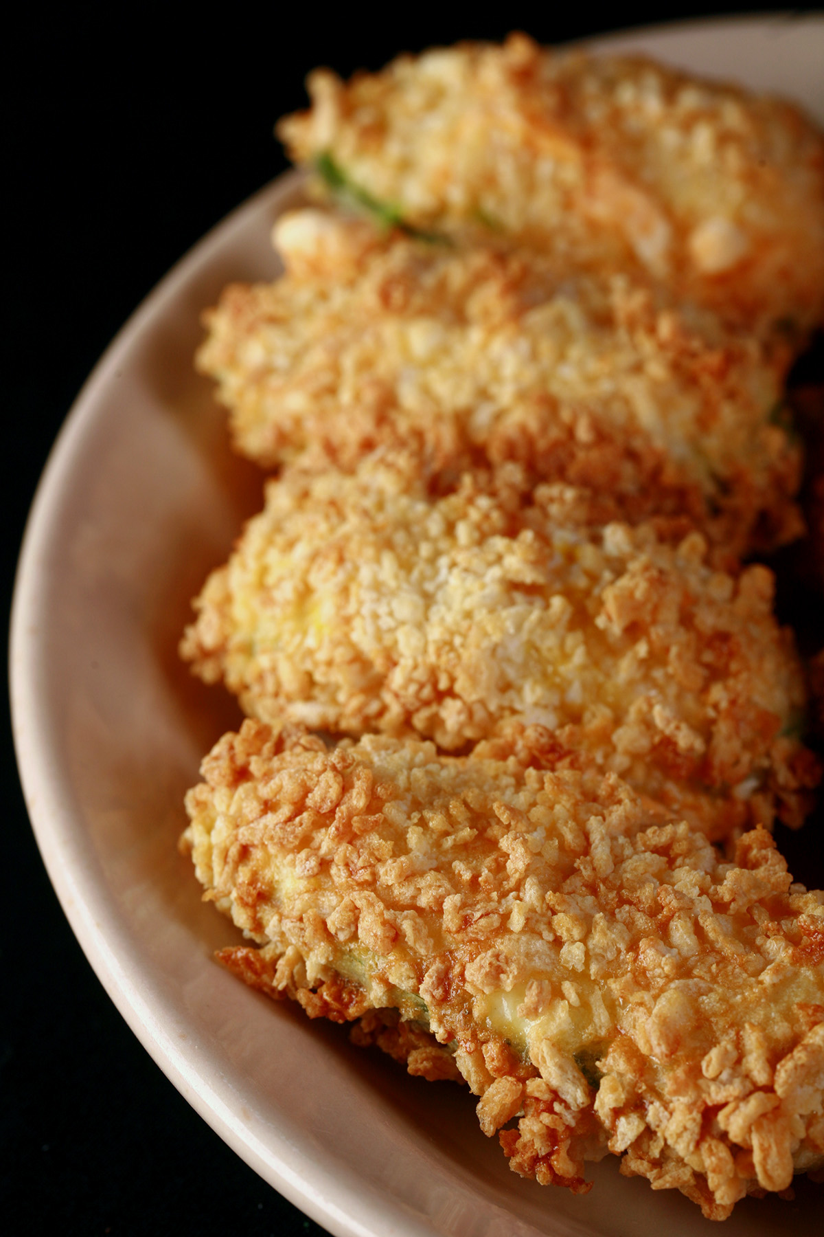 Air fried gluten free jalapeno poppers on a small ivory plate. These 4 are coated in gluten-free panko crumbs.