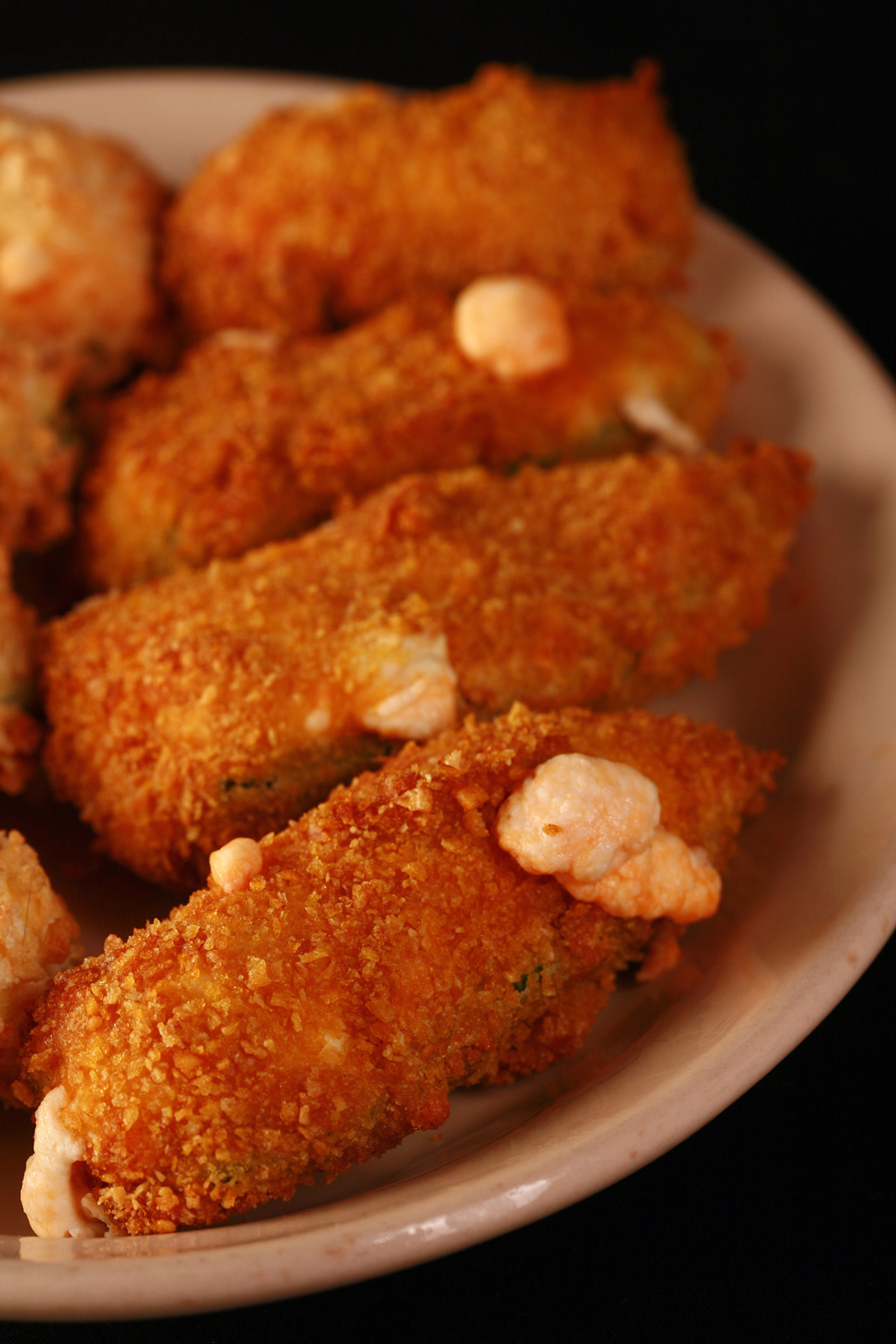 Air fried gluten free jalapeno poppers on a small ivory plate. These 4 are coated in corn flake crumbs.