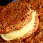 A small blue and white plate with a stack of gluten-free carrot cake cookies on it. The filling is ivory coloured and has flecks of orange zest throughout
