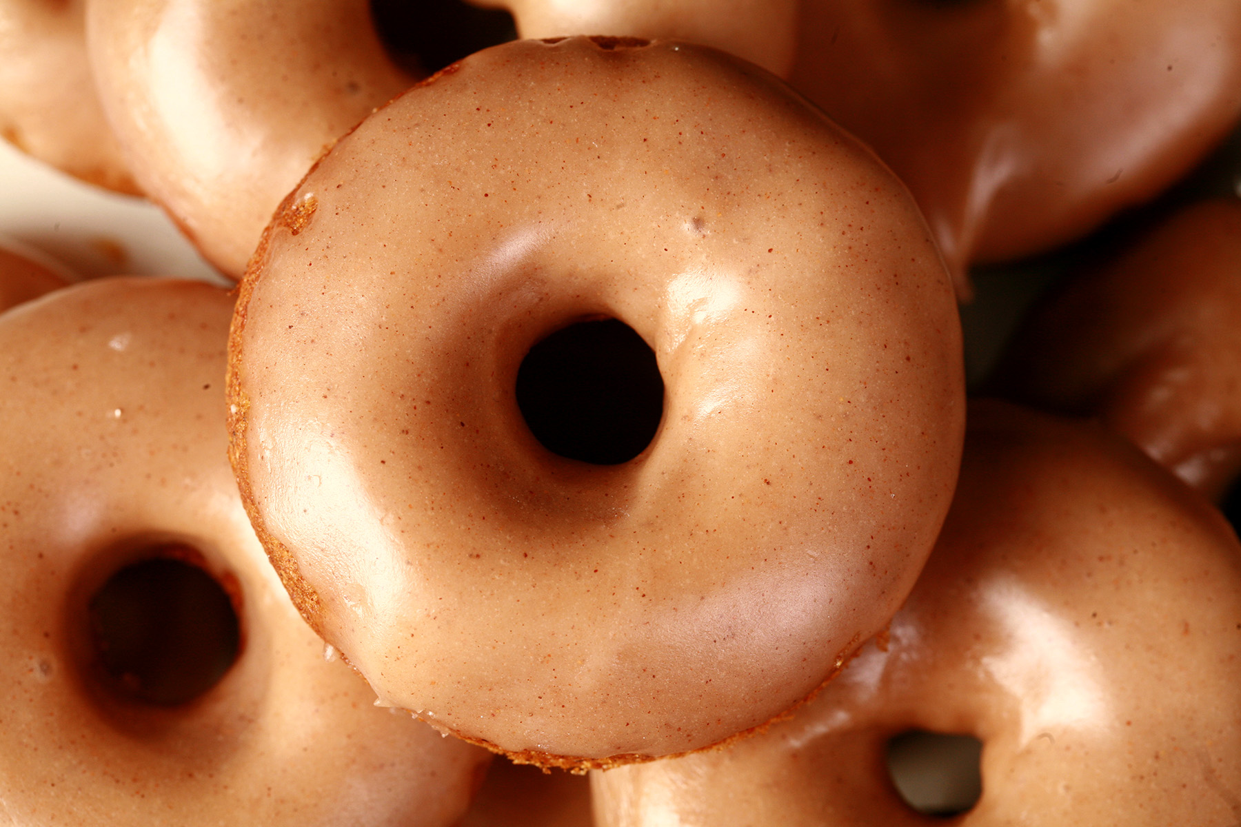 Close up view of gluten-free pumpkin spice mini doughnuts. They are glazed with a tan coloured maple frosting.