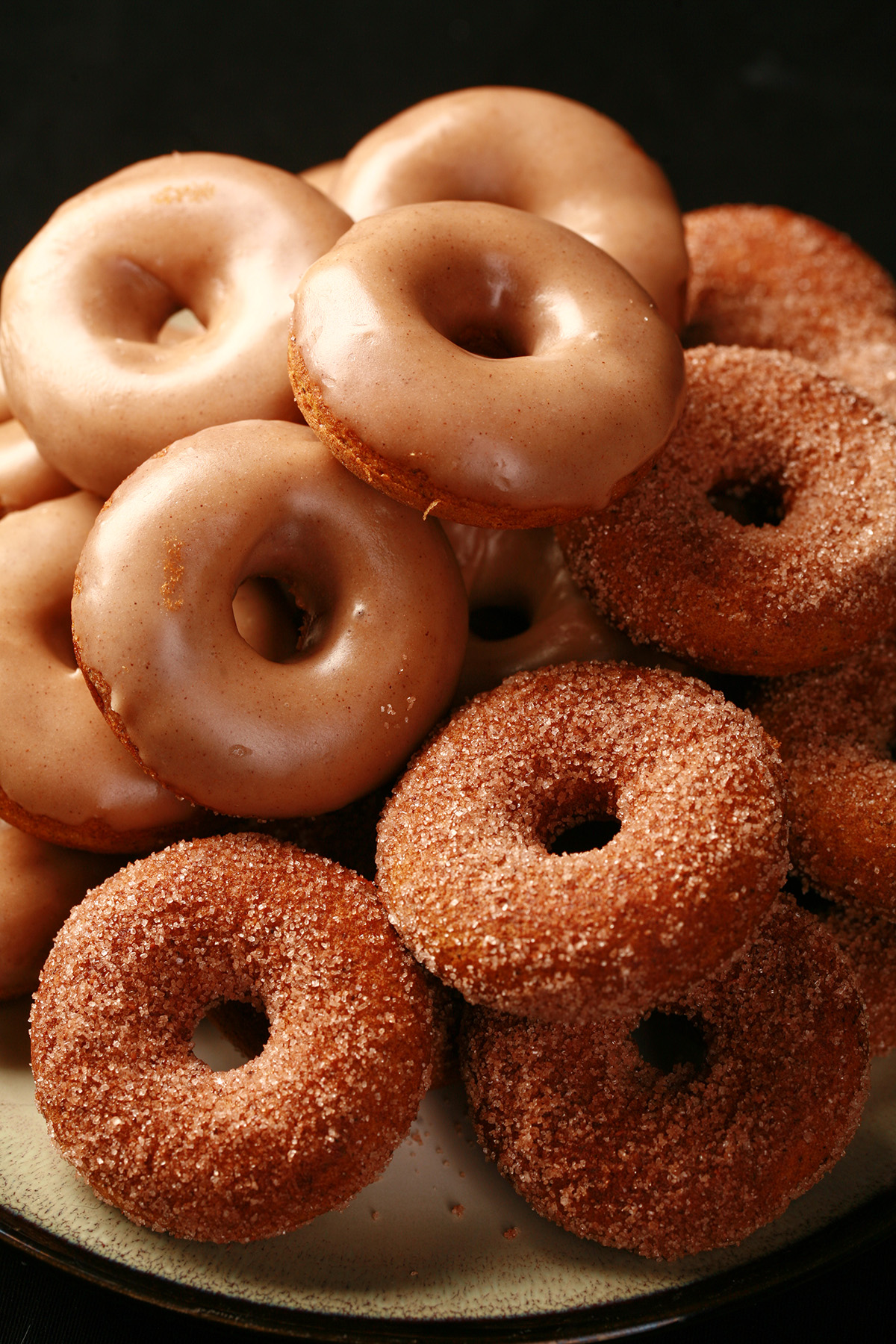 Close up view of gluten-free pumpkin spice mini doughnuts. Some are coated in cinnamon sugar, others are glazed with a tan coloured frosting.