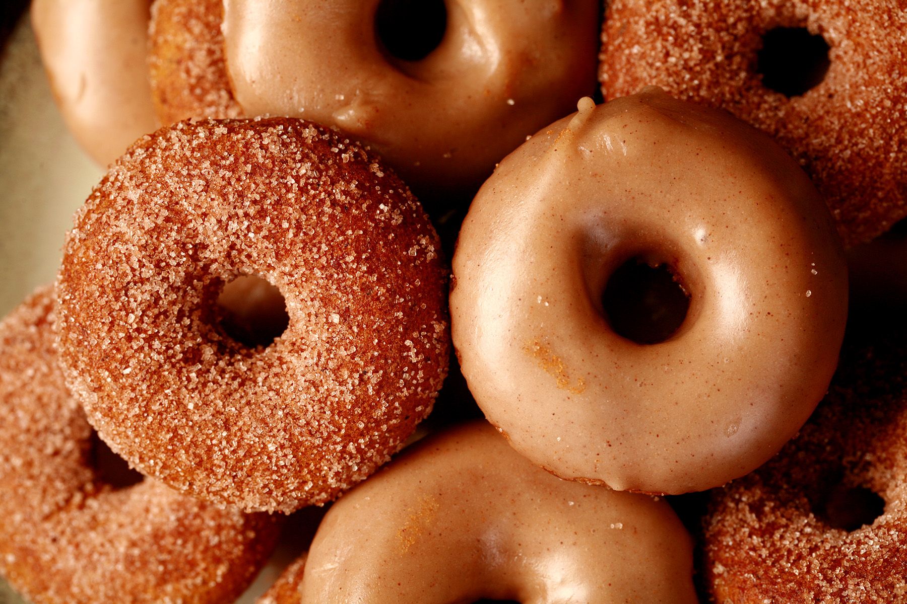Close up view of gluten-free pumpkin spice mini doughnuts. Some are coated in cinnamon sugar, others are glazed with a tan coloured frosting
