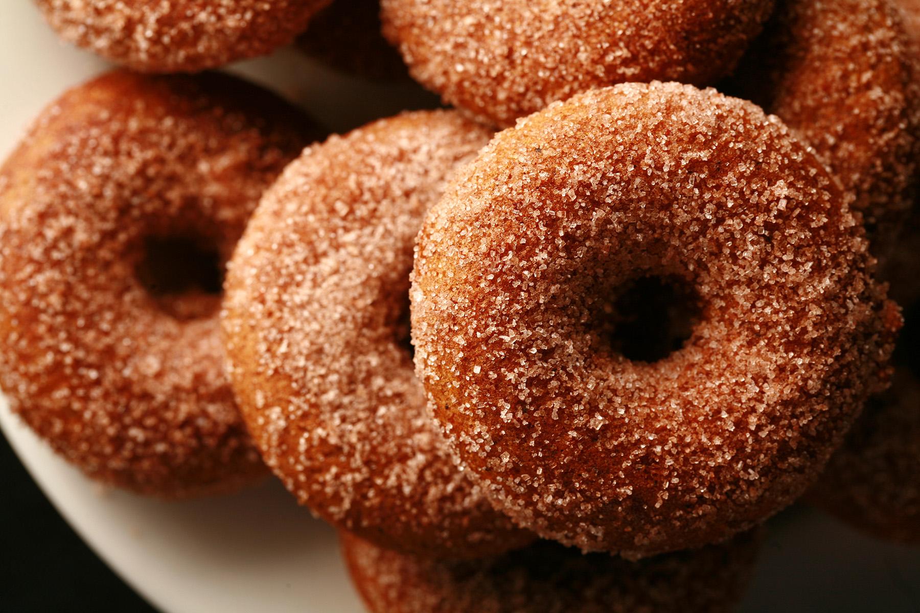 """""""Close up view of gluten-free pumpkin spice mini doughnuts, coated in cinnamon sugar"""