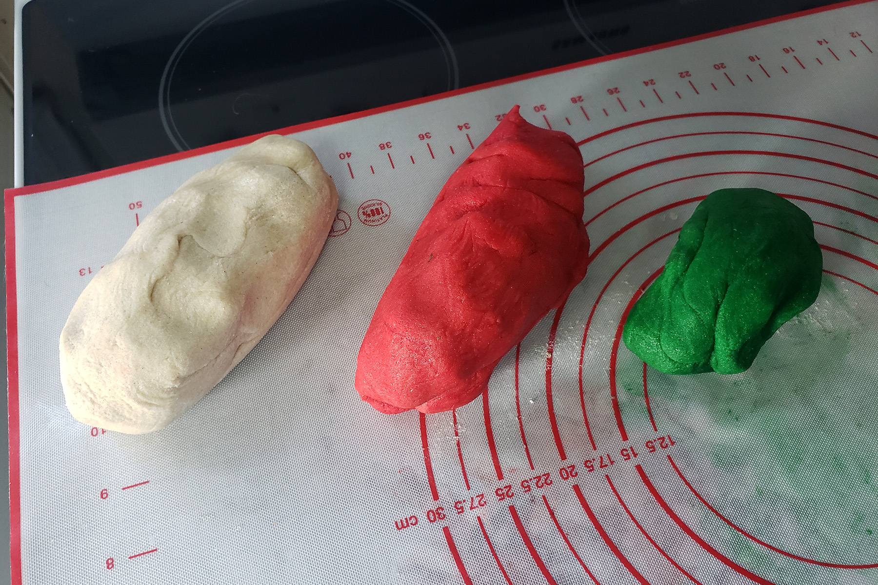 Lumps of white, red, and green dough rest on a silicone baking mat.