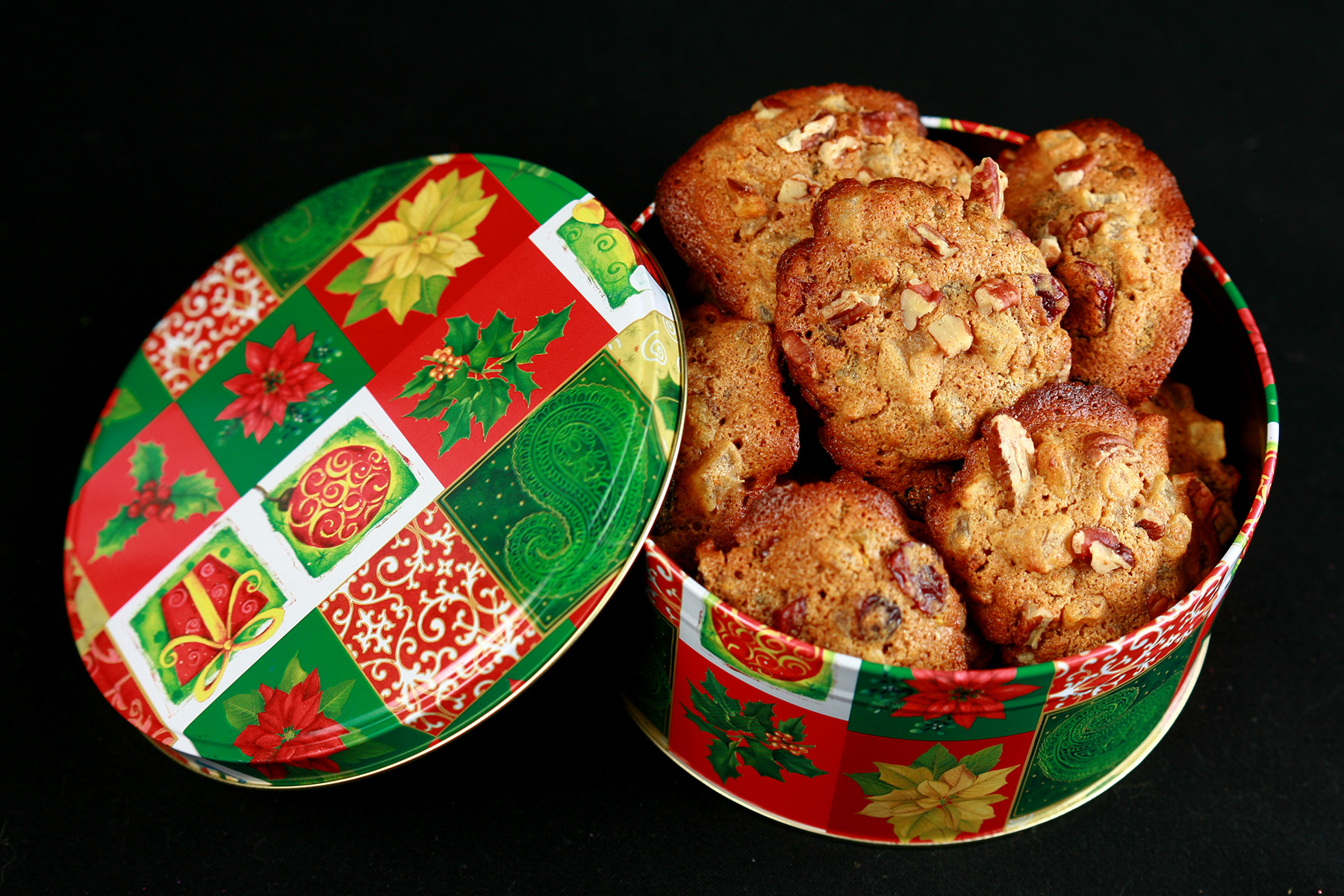A festive green and red holiday container is full of cookies. The cookies have visible pieces of fruits and nuts throughout.