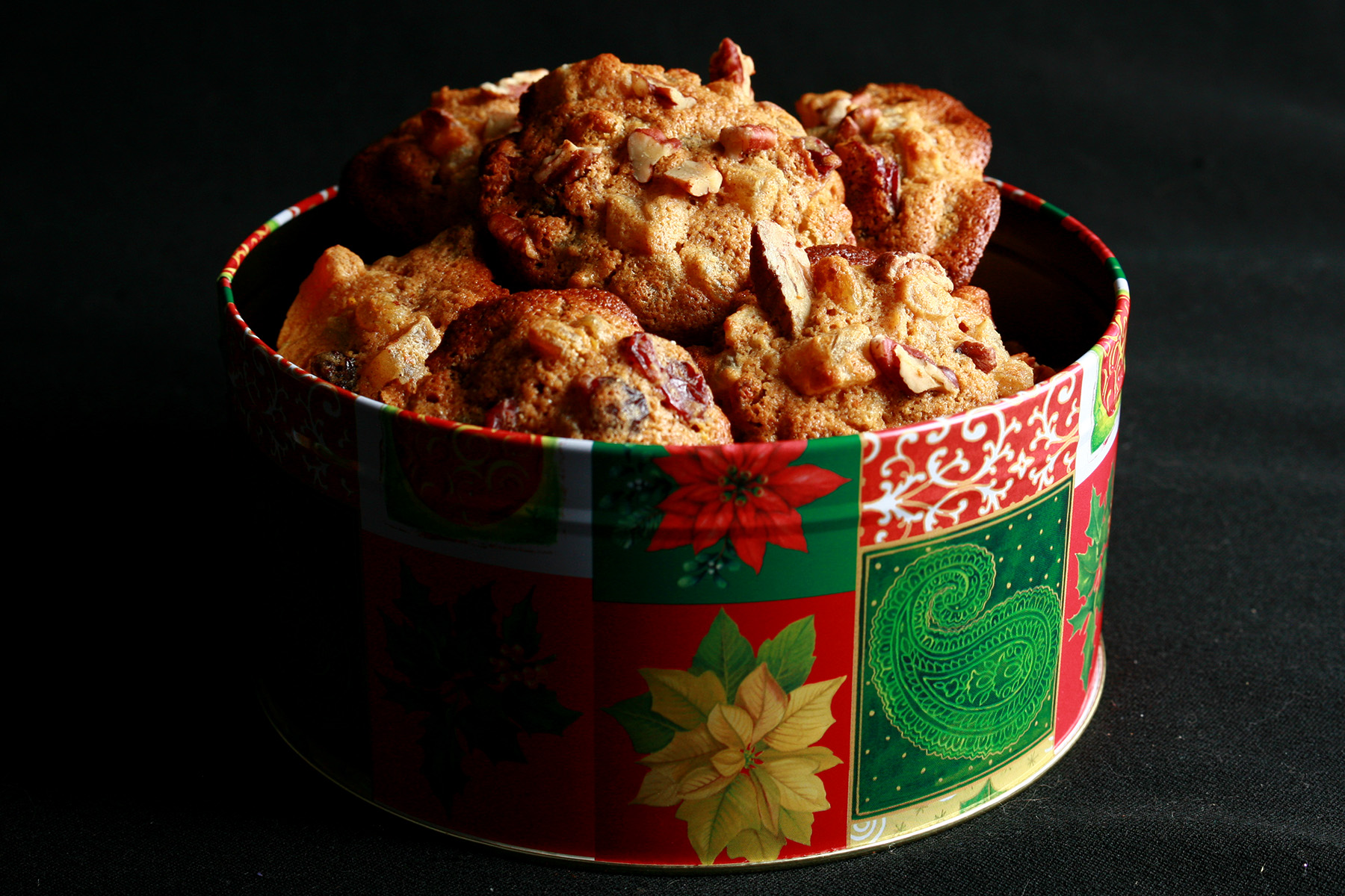 """""""A festive green and red holiday container is full of cookies. The cookies have visible pieces of fruits and nuts throughout."""