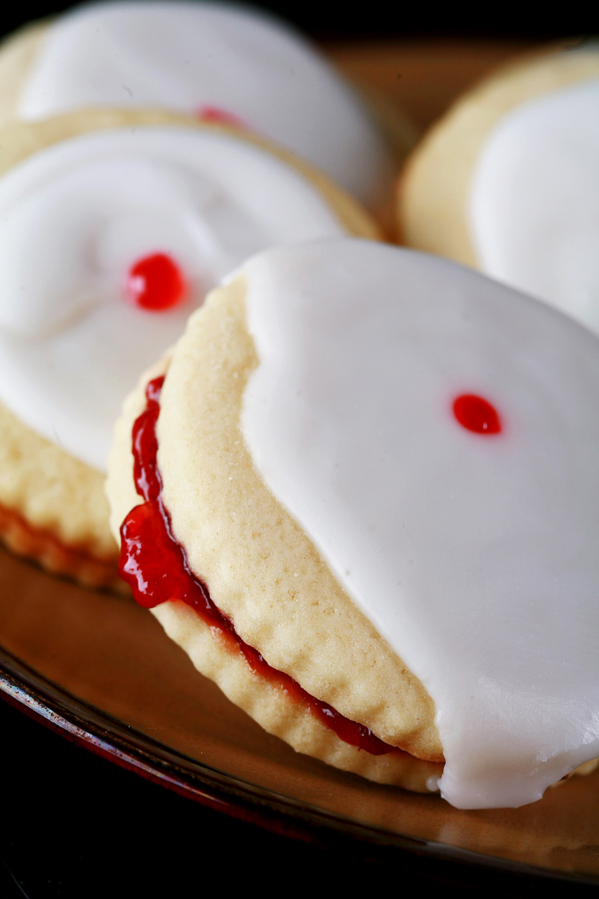 Close up view of a plate of gluten-free imperial cookies: Sandwich cookies filled with raspberry jam, frosted with a white glaze, and finished off with a dot of red gel in the center.