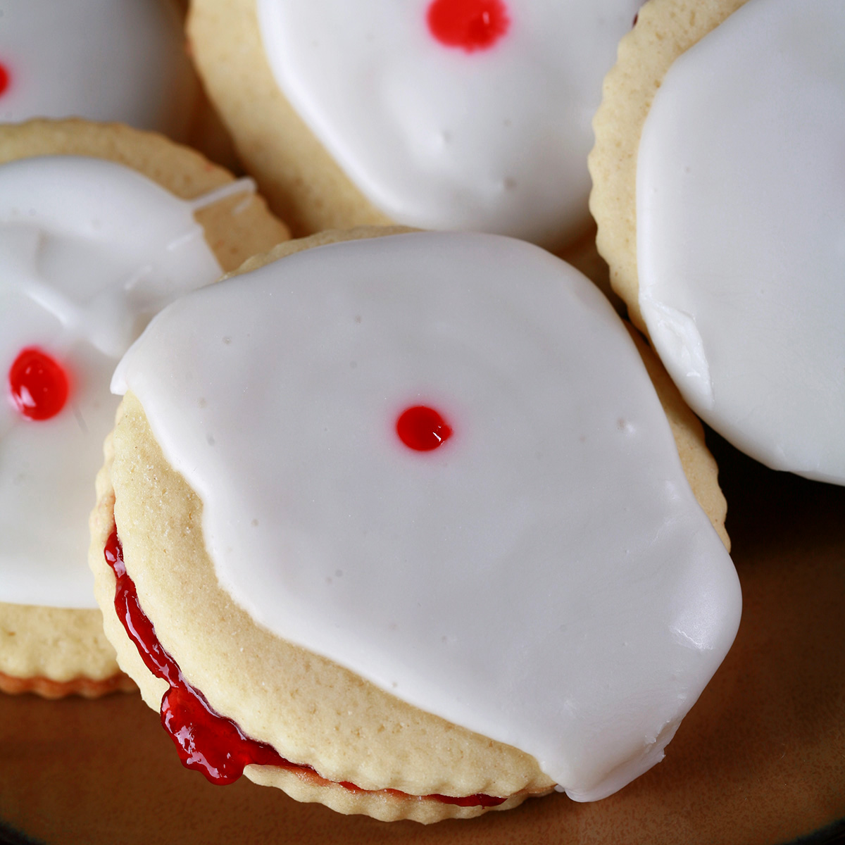 """Close up view of a plate of Gluten-Free Empire Cookies - sandwich cookies filled with raspberry jam, frosted with a white glaze, and finished off with a dot of red gel in the center."