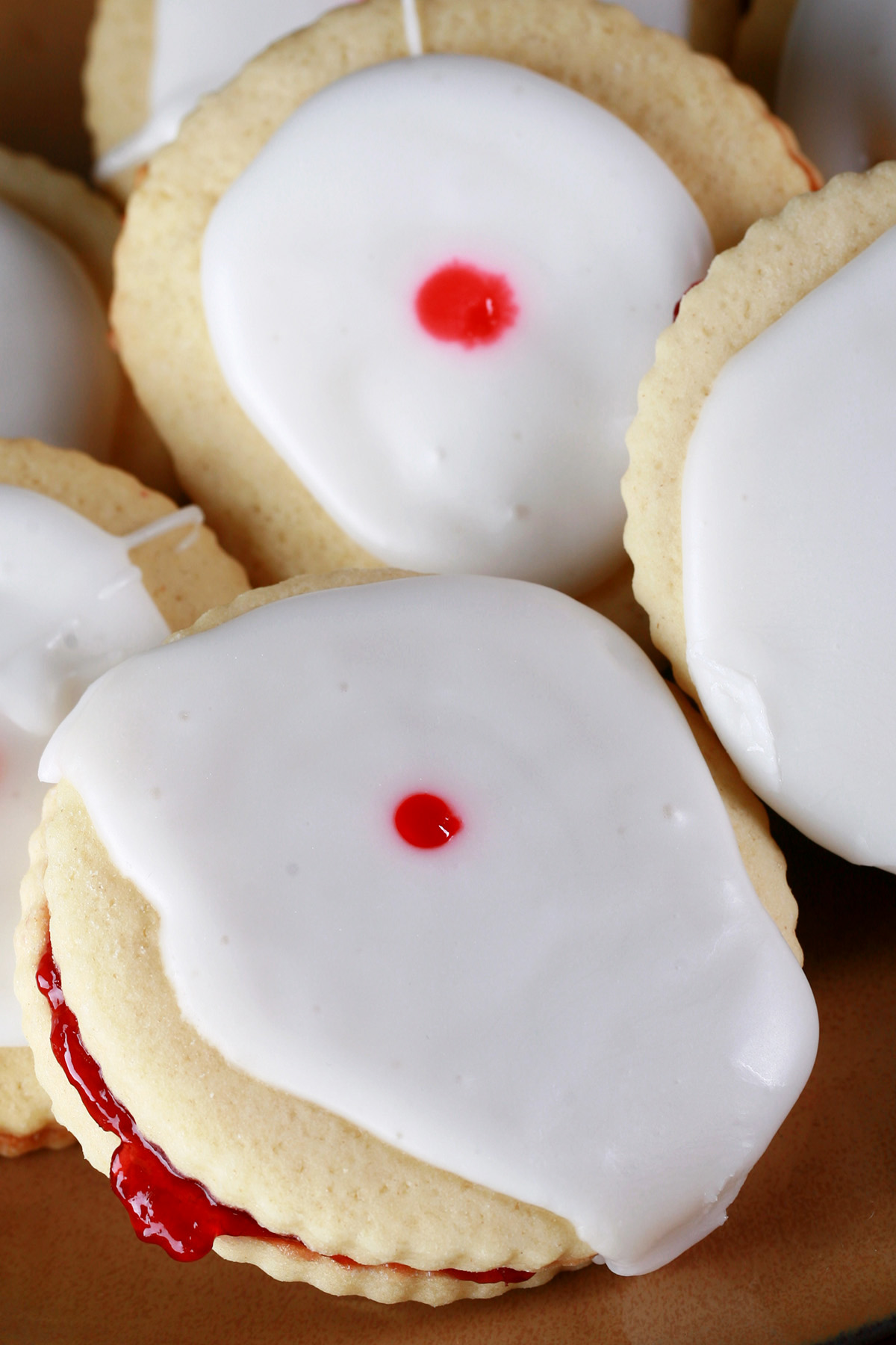 Close up view of a plate of Gluten-Free Empire Biscuits - sandwich cookies filled with raspberry jam, frosted with a white glaze, and finished off with a dot of red gel in the center.