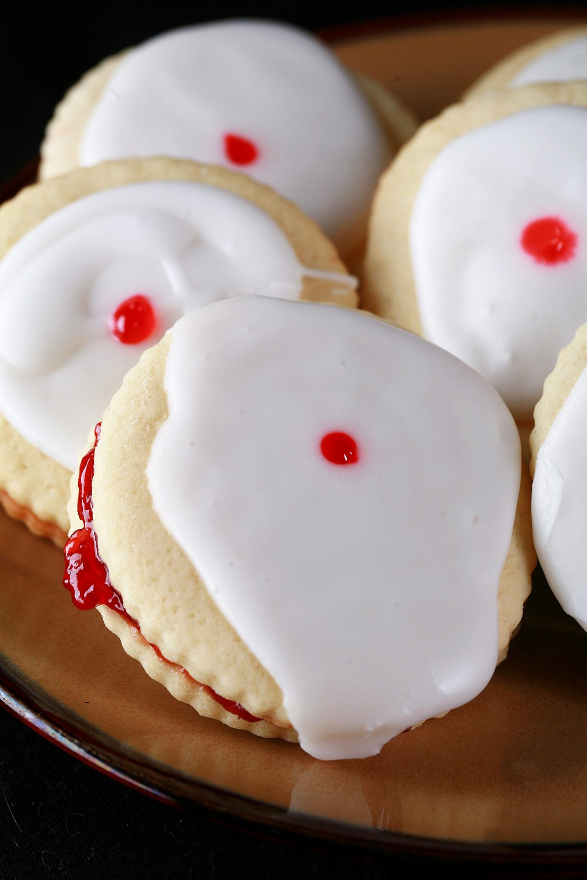 Close up view of a plate of Gluten-Free Empire Cookies - sandwich cookies filled with raspberry jam, frosted with a white glaze, and finished off with a dot of red gel in the center.