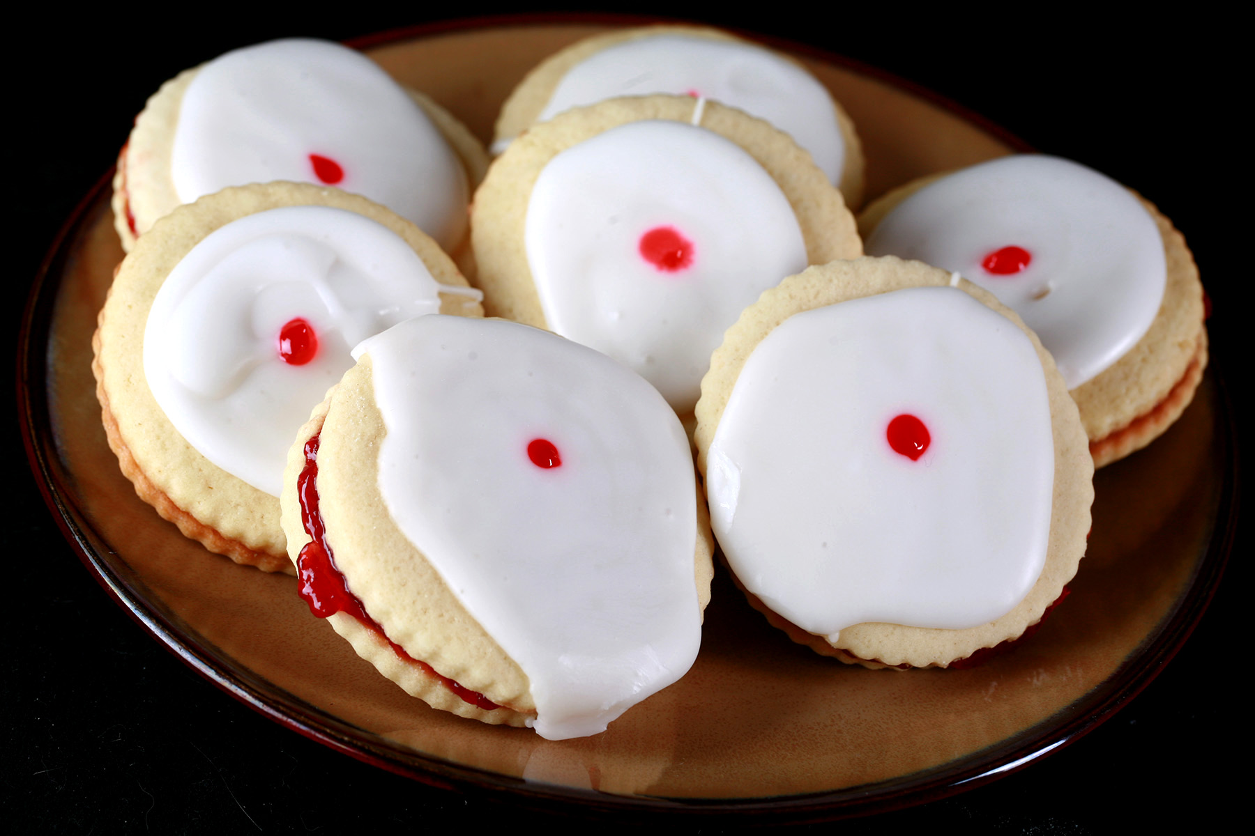 """Close up view of a plate of gluten-free imperial cookies: Sandwich cookies filled with raspberry jam, frosted with a white glaze, and finished off with a dot of red gel in the center."