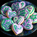 Close up view of a plate of heart shaped gluten-free sugar cookies. They are decorated with swirls of teal and lavender over a base of white frosting.