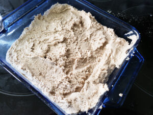 Raw biscuit dough spread in a square pan.