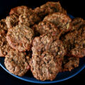 A large blue plate piled with Chewy Gluten-Free Banana Oatmeal cookies, against a black background.