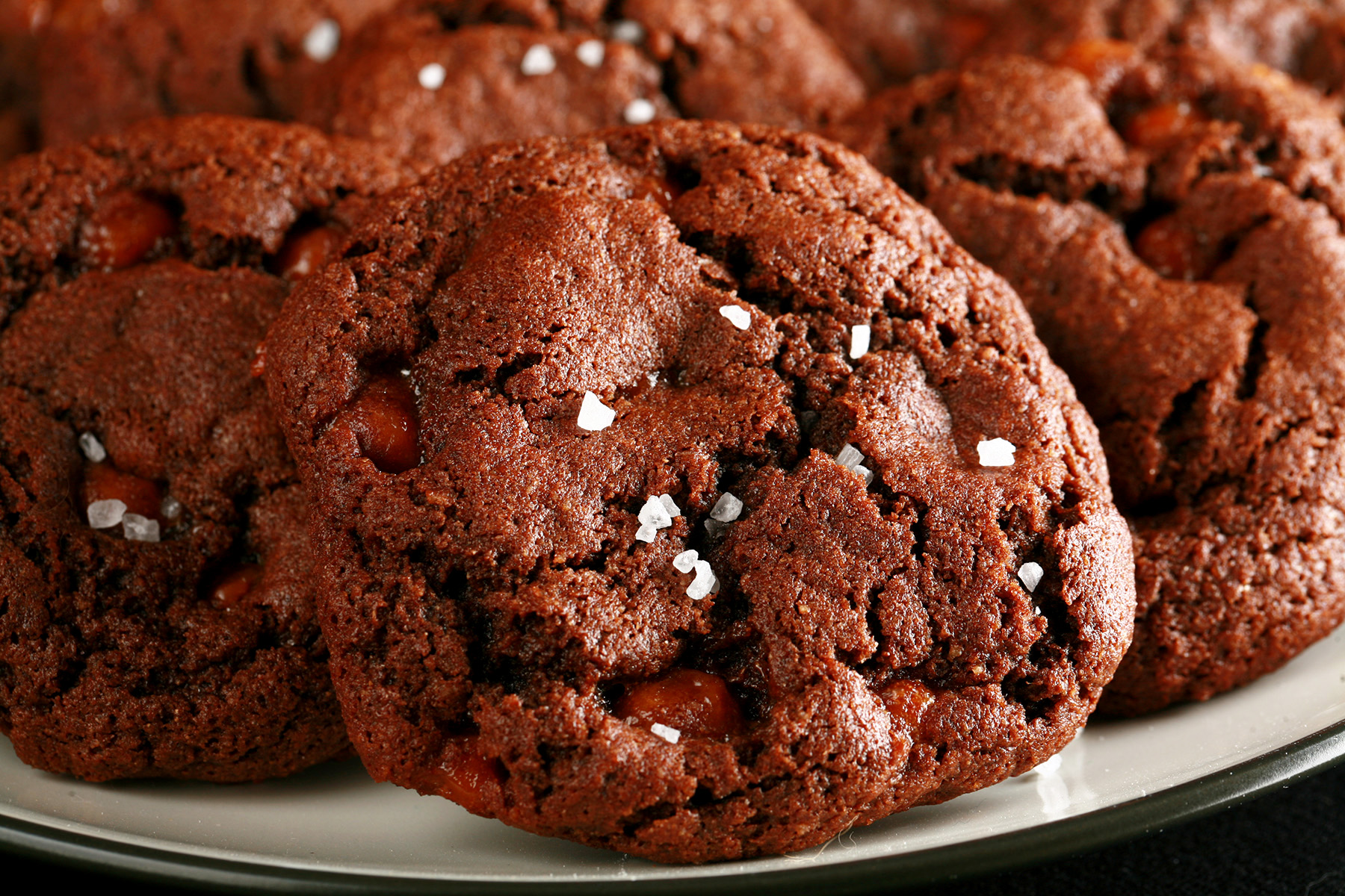 A small white plate, piled with Chewy, Gluten-Free Chocolate Cookies. Bits of caramel are visible within the cookies, and each is topped with a sprinkle of sea salt.