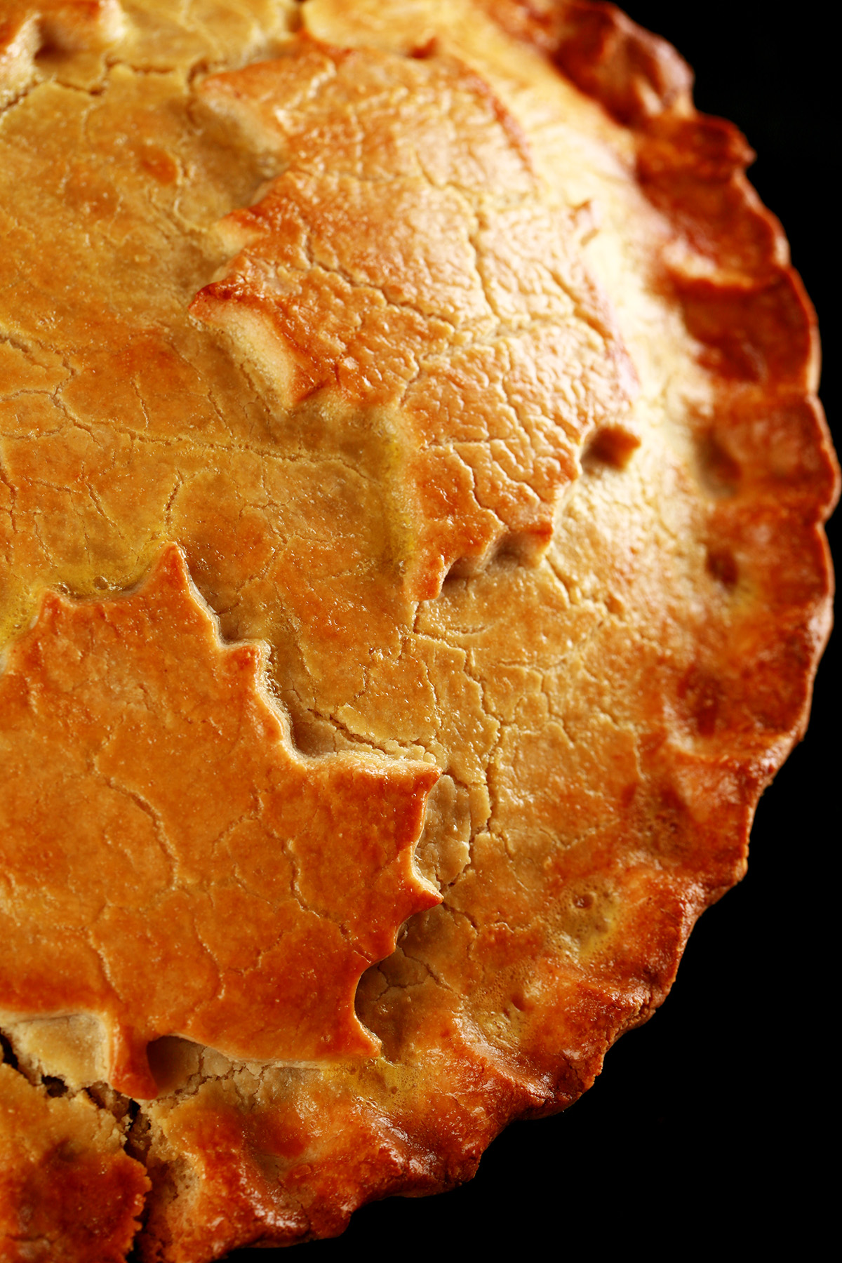 A close up photo of a cut-open chicken mushroom tourtiere pie. The crust has maple leaves on it.