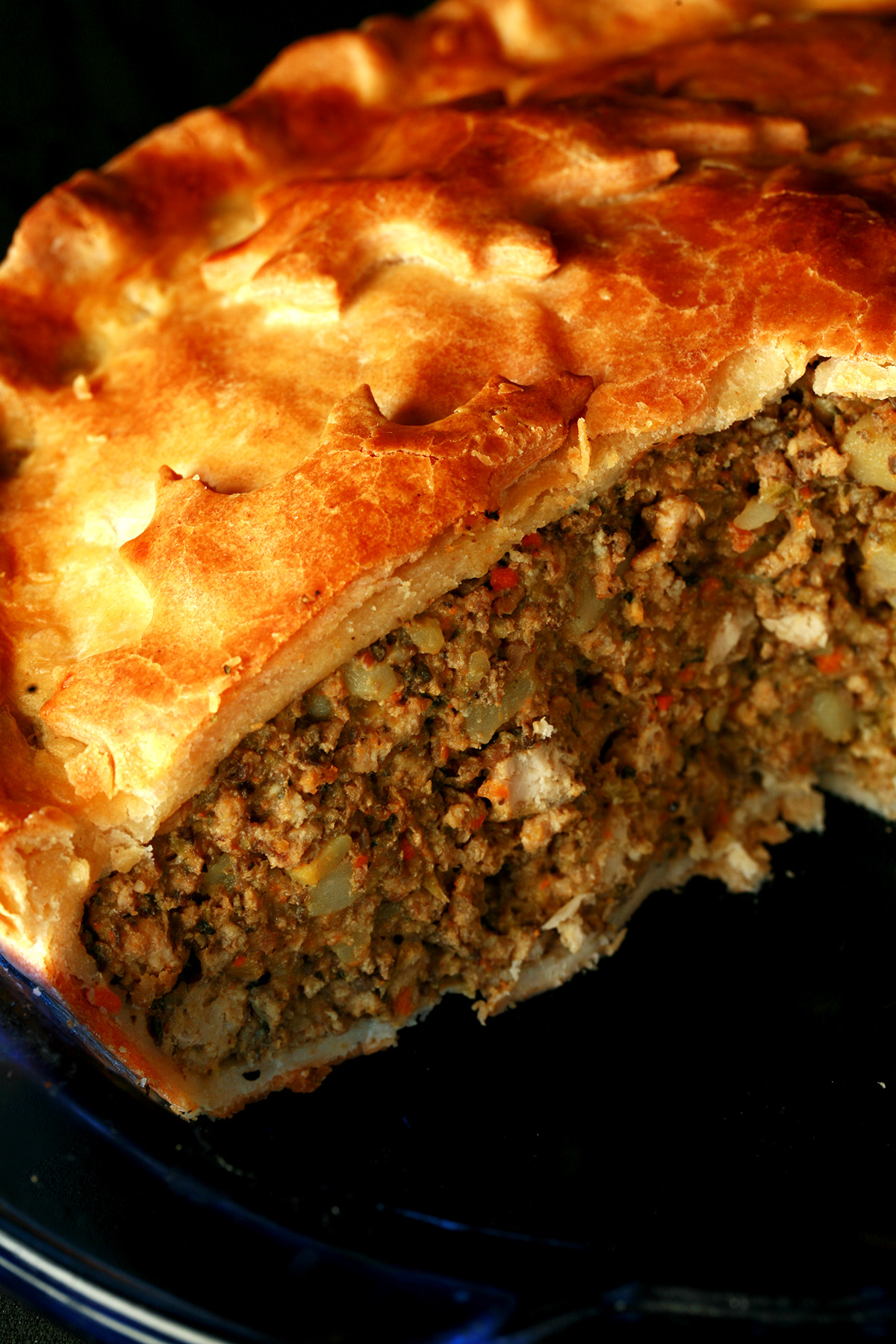 A close up photo of a cut-open meat pie. The crust has maple leaves on it.