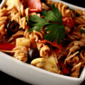 A rich looking pasta salad in a white bowl. Spiral noodles are shown lgthly coated in a thin red sauce, with pepperoni, artichoked, black olives, cheese, and parsley visible.