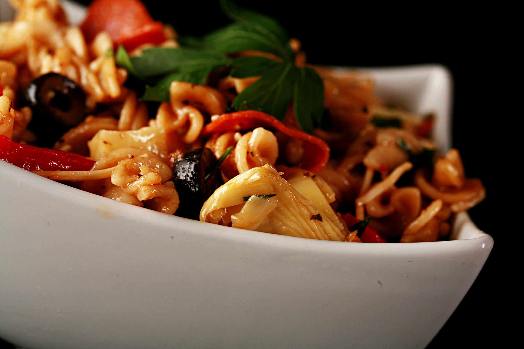 A rich looking pasta salad in a white bowl. Spiral noodles are shown lgthly coated in a thin red sauce, with pepperoni, artichokes, black olives, cheese, and parsley visible.""