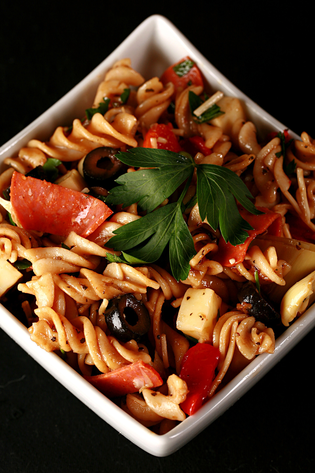 Gluten-free antipasto pasta salad in a white bowl. Spiral noodles are shown lgthly coated in a thin red sauce, with pepperoni, artichoked, black olives, cheese, and parsley visible.