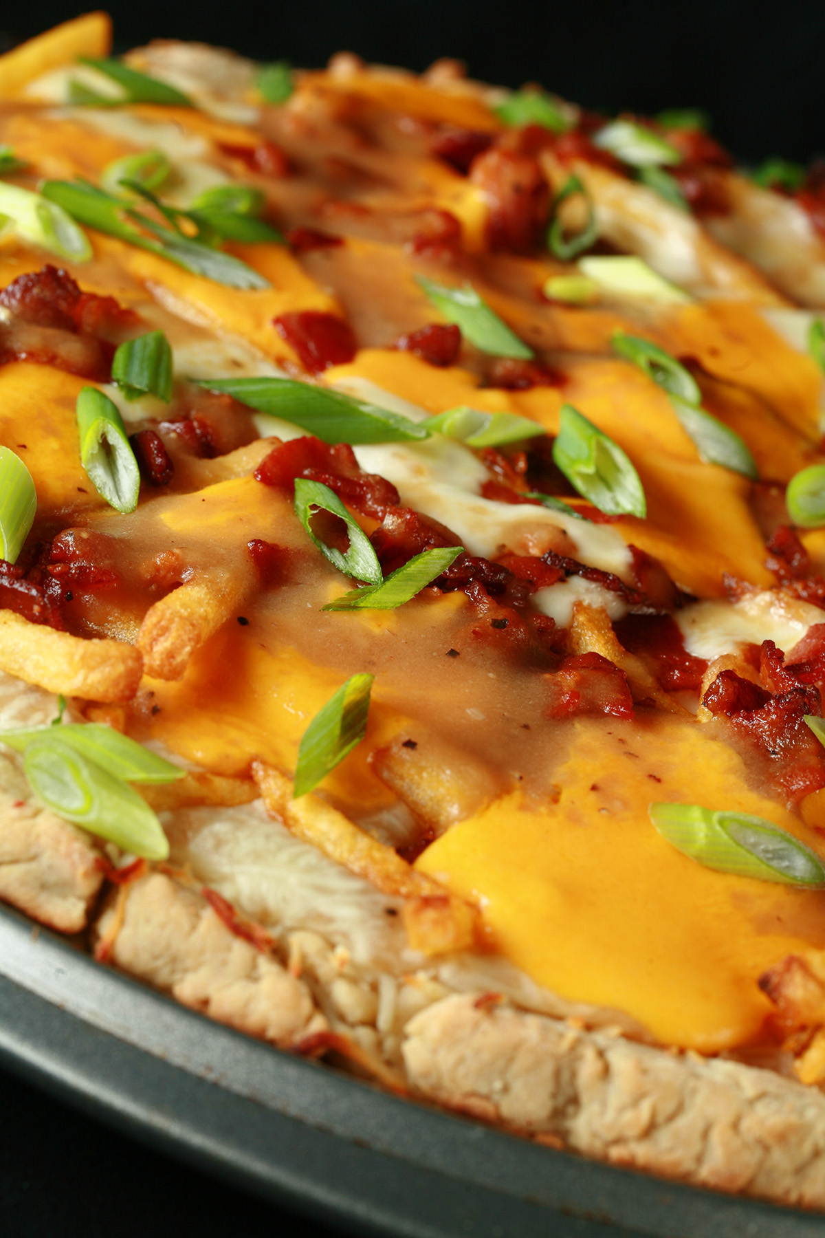 A close up view of a gluten-free bacon poutine pizza - A pizza crust topped with gravy, fries, cheese curds, chredded cheese, bacon, and green onions!