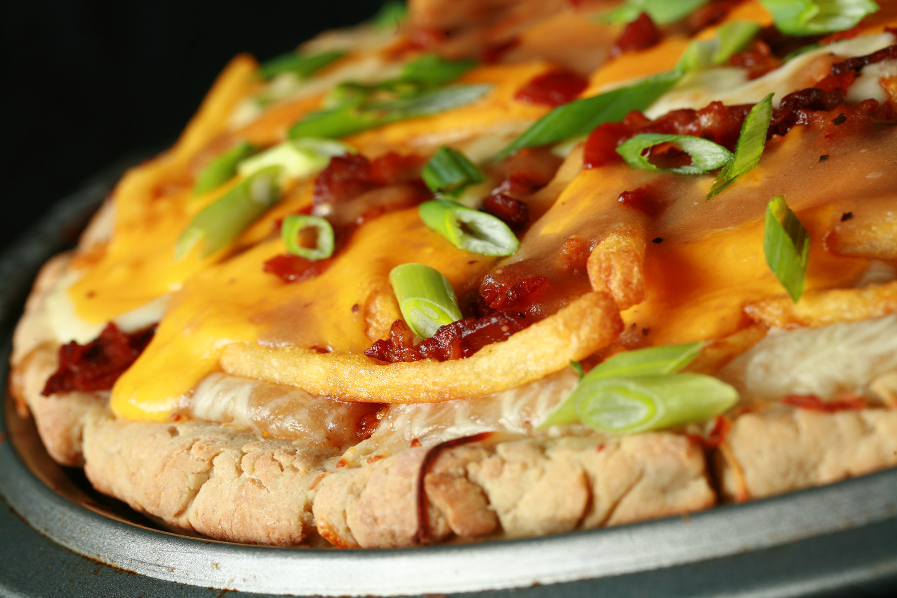 A close up view of a gluten-free poutine pizza - A pizza crust topped with gravy, fries, cheese curds, chredded cheese, bacon, and green onions!