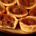 A brown plate is crowded with gluten-free buttertarts - mini tarts with a gooey sugar filling and raisins.
