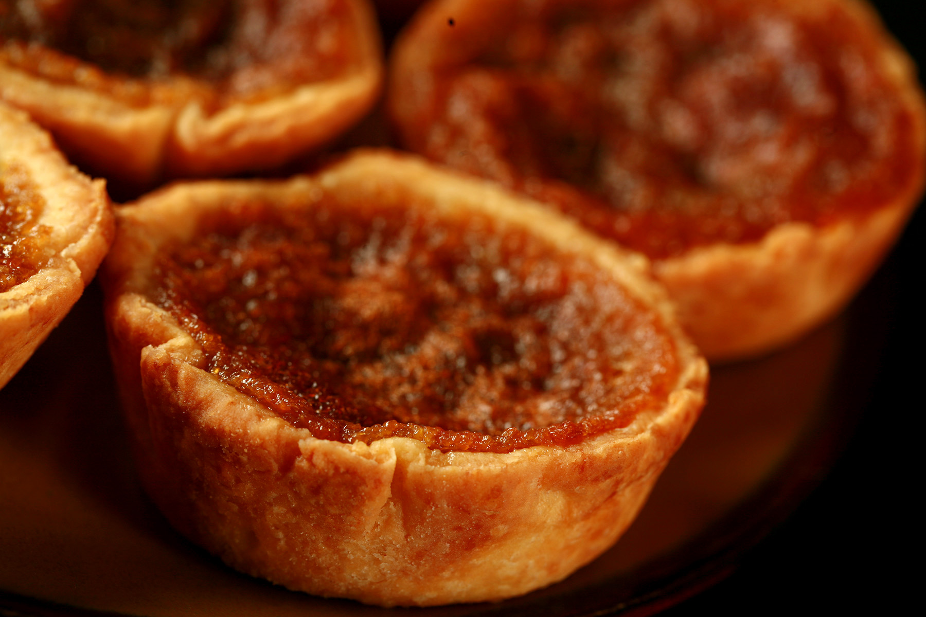 A brown plate is crowded with gluten-free butter tarts - mini tarts with a gooey sugar filling and raisins