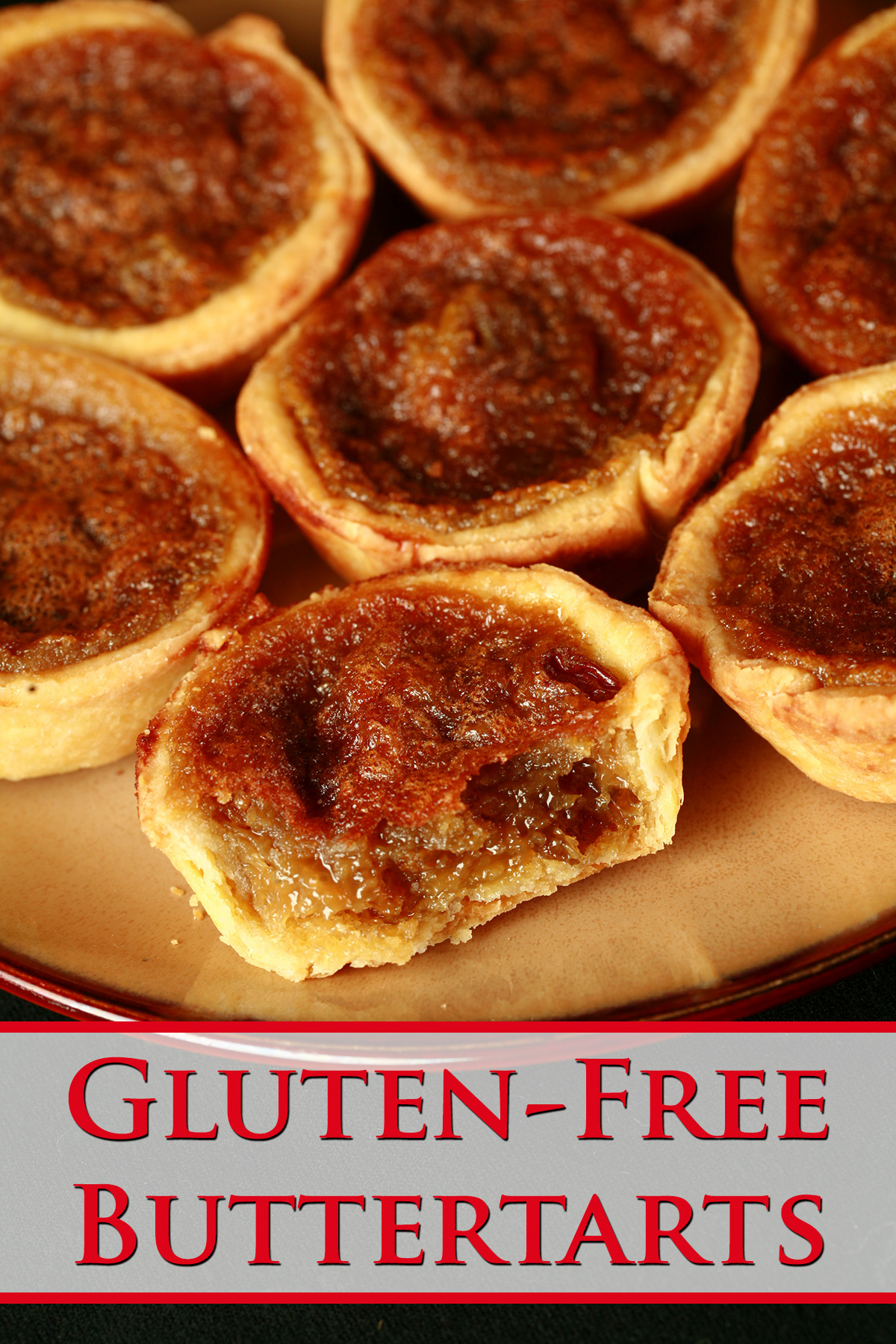 A brown plate is crowded with gluten-free buttertarts - mini tarts with a gooey sugar filling and raisins