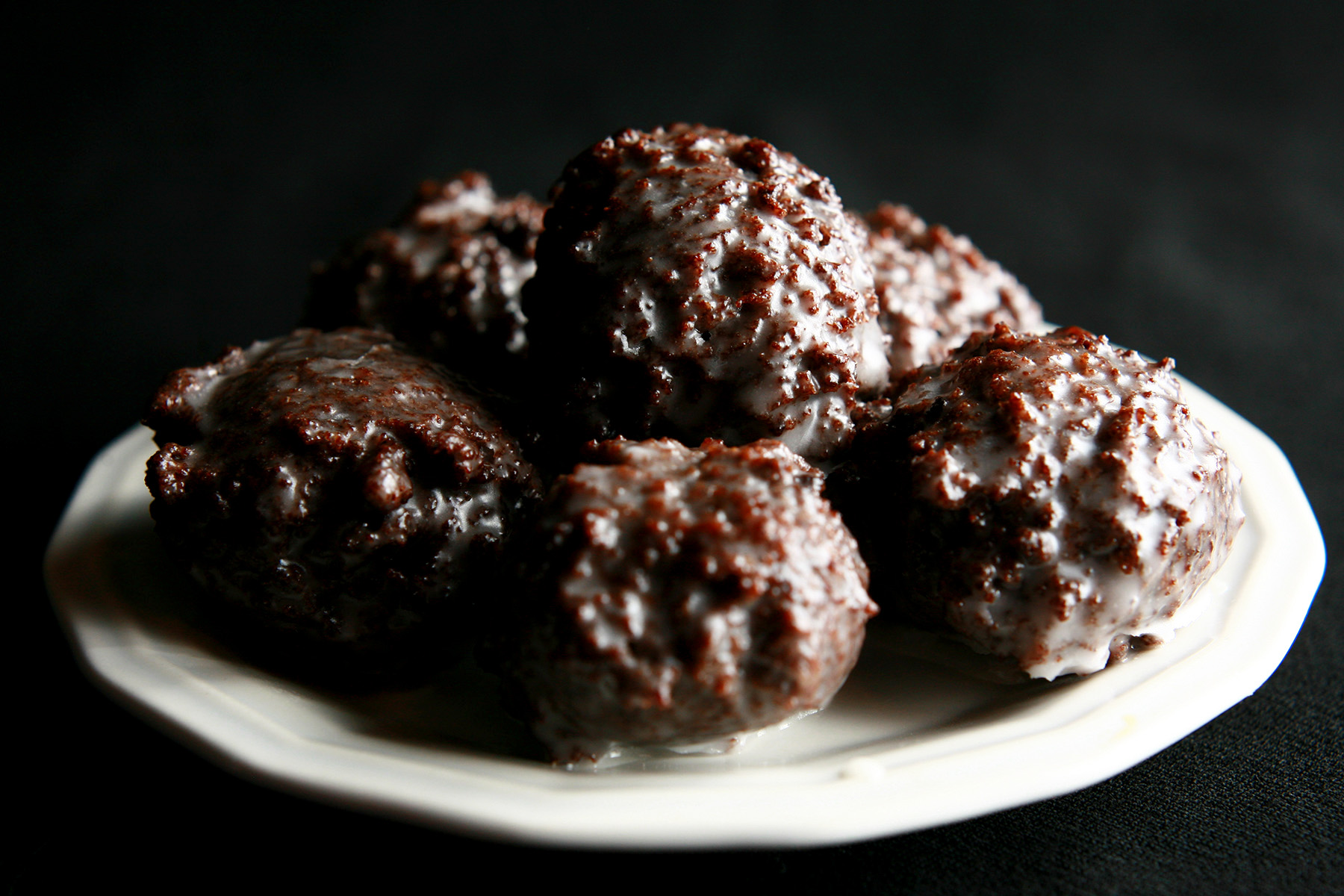 Several gluten-free chocolate doughnut holes on a small white plate.