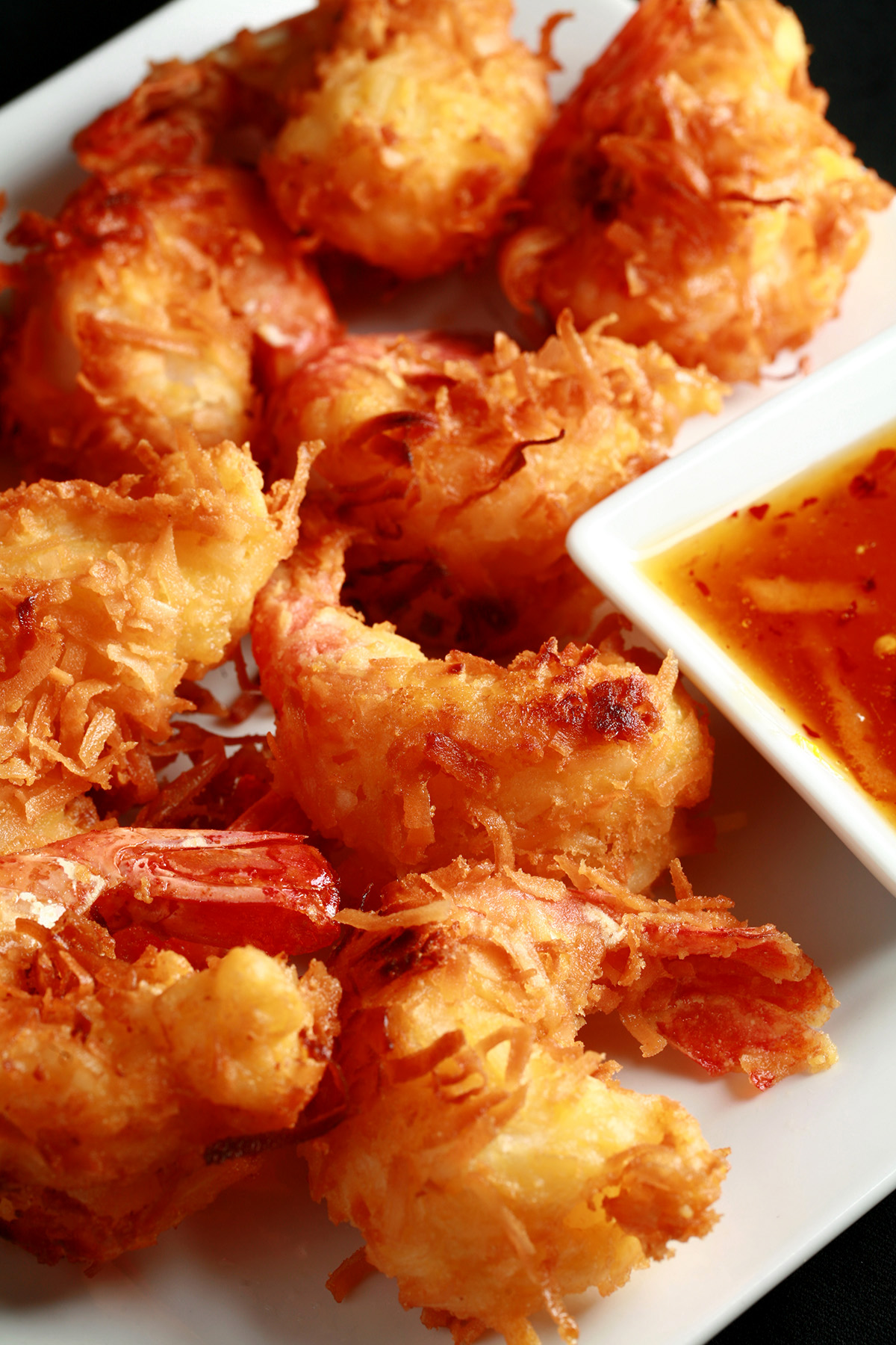 A white plate is covered with golden brown gluten-free coconut shrimp.  There is a small bowl of spicy ginger-orange sauce on the same plate, as a dip.