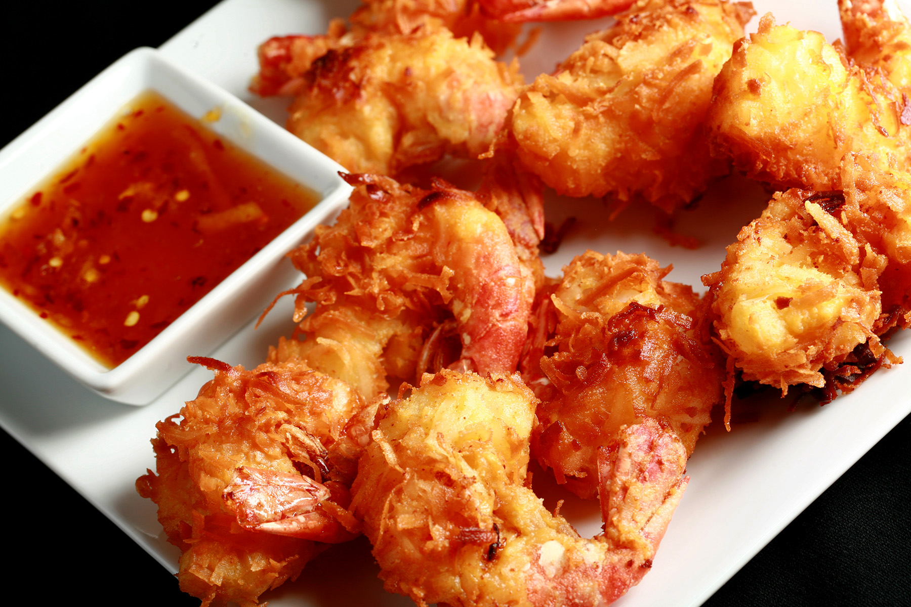 """A white plate is covered with golden brown gluten-free coconut shrimp.  There is a small bowl of spicy ginger-orange sauce on the same plate, as a dip."