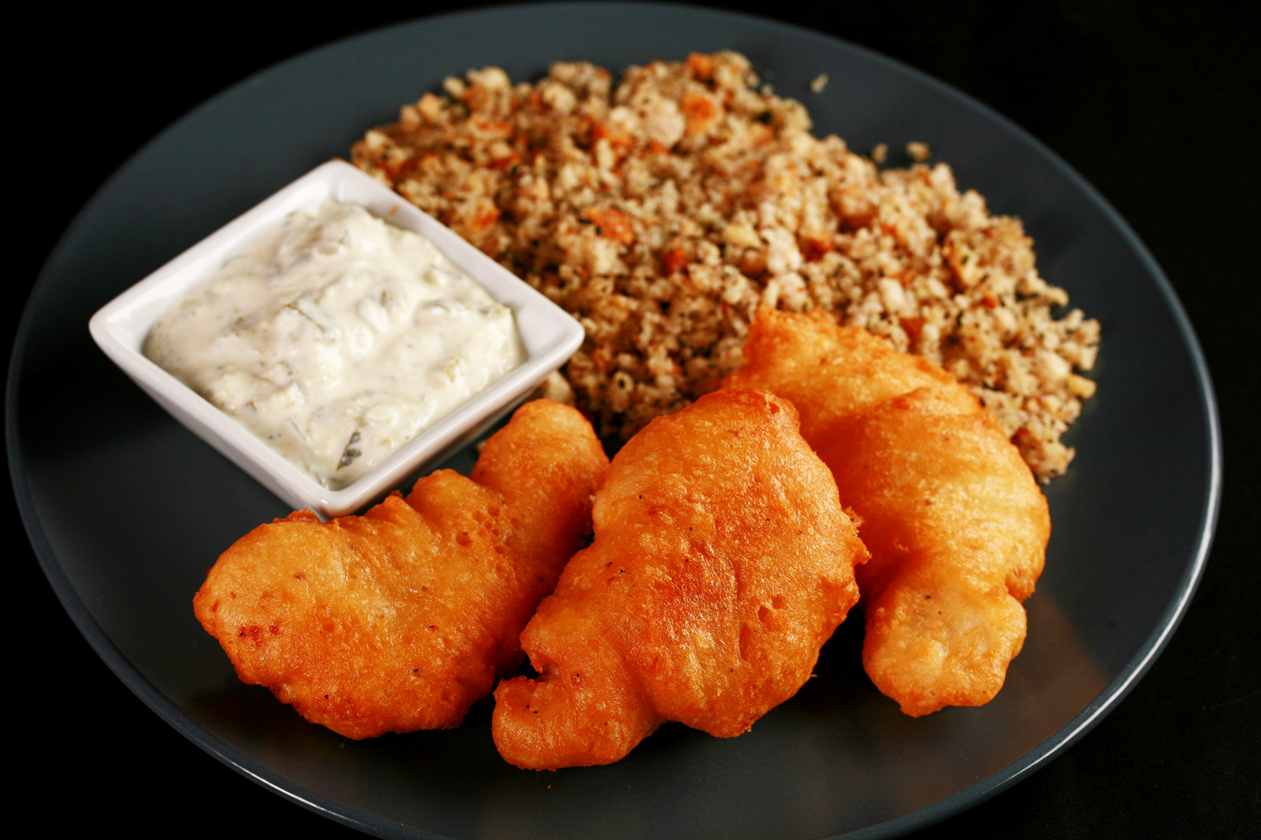 Gluten-Free Cod Cheeks and Dressing, on a round, blue plate. There is a small dish of tartar sauce on the plate, as well.