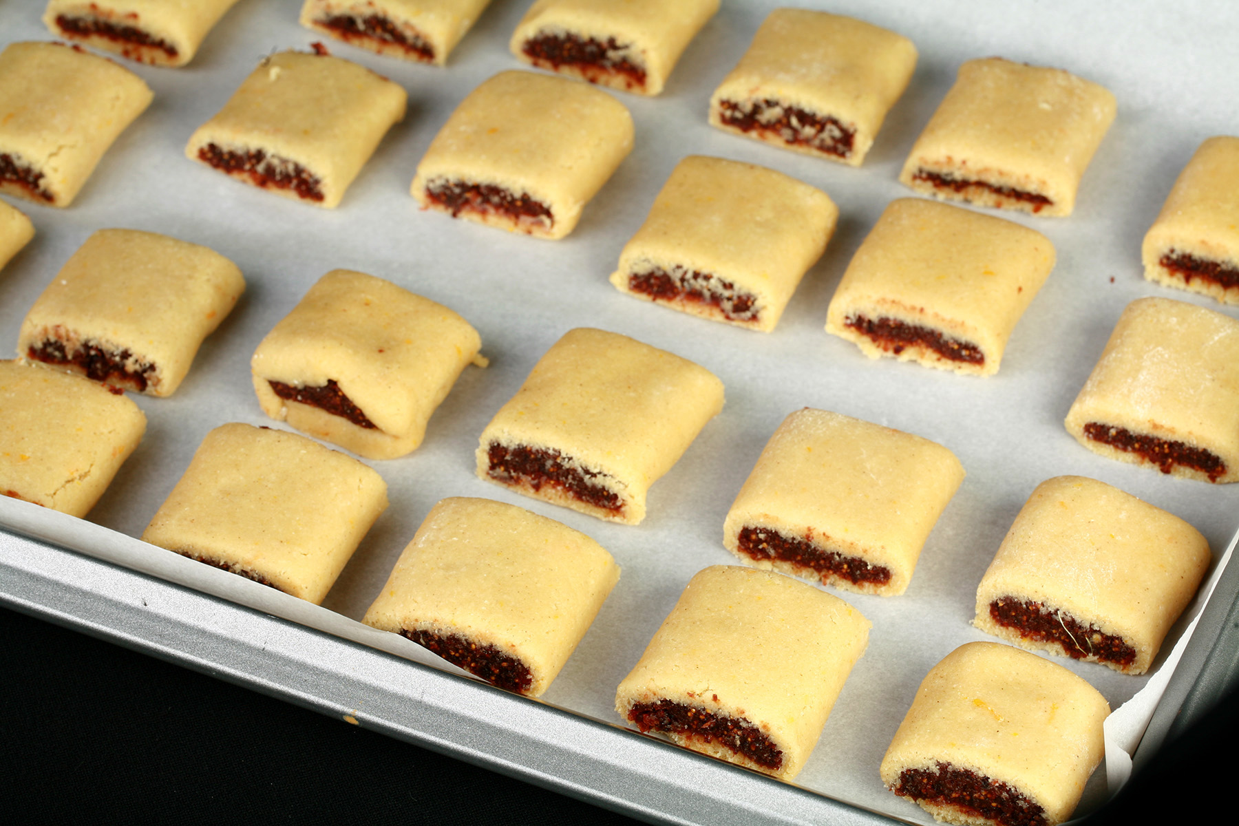 Rows of raw fig newton cookies, lined up on a parchment lined baking sheet.
