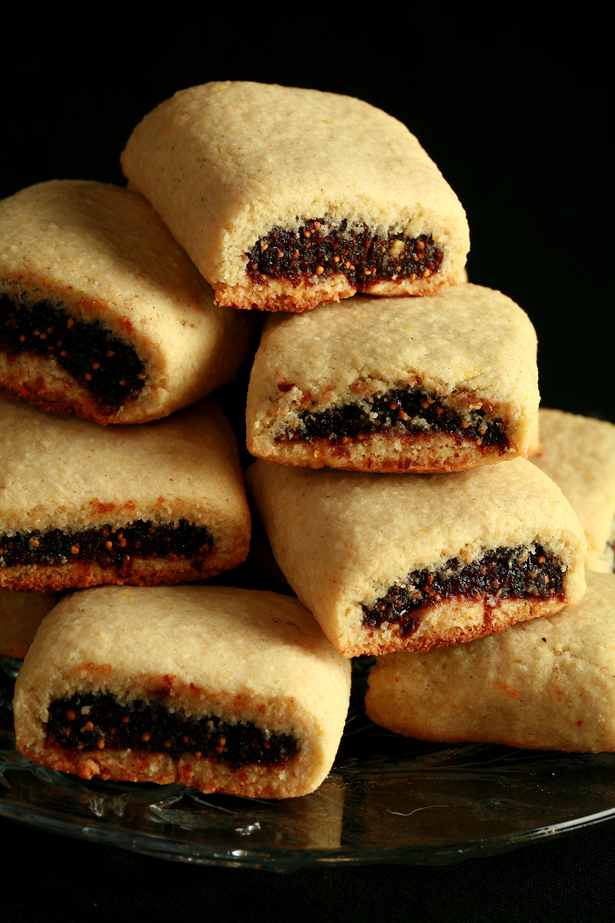 A small glass plate piled high with gluten-free fig newton cookies.