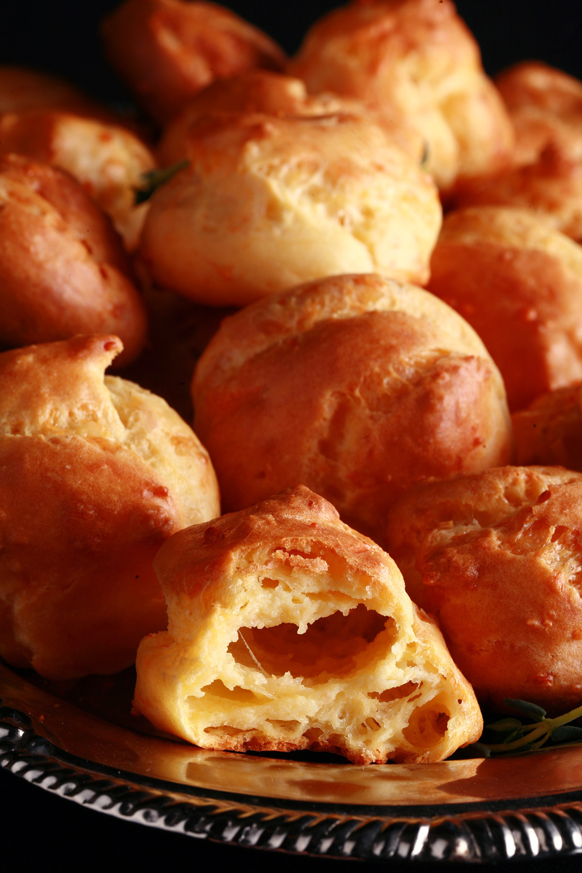 A large pile of Gluten-free Gougères - small, cheesy pastries - on a silver plate.