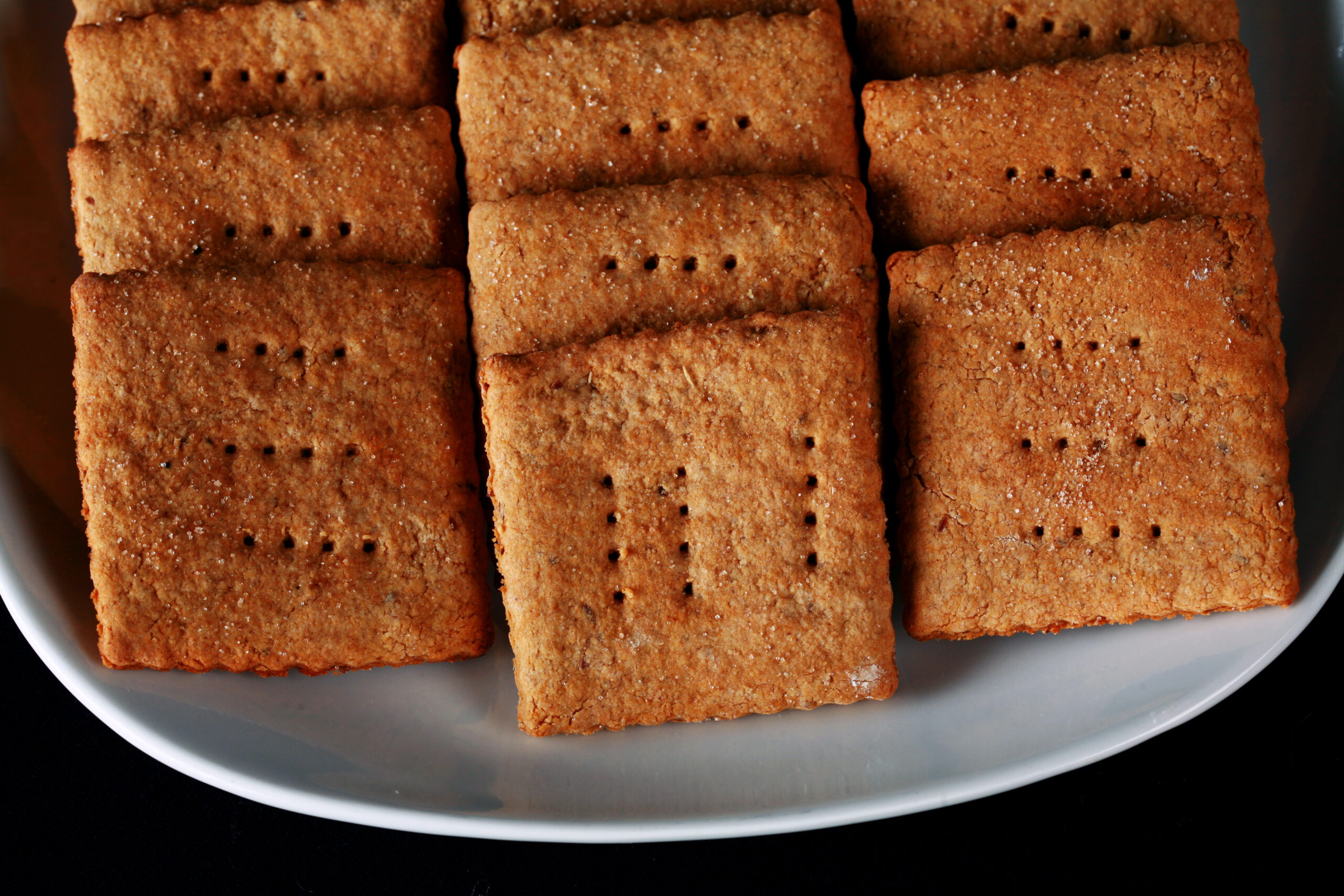A white plate with rows of square shaped gluten-free graham crackers.