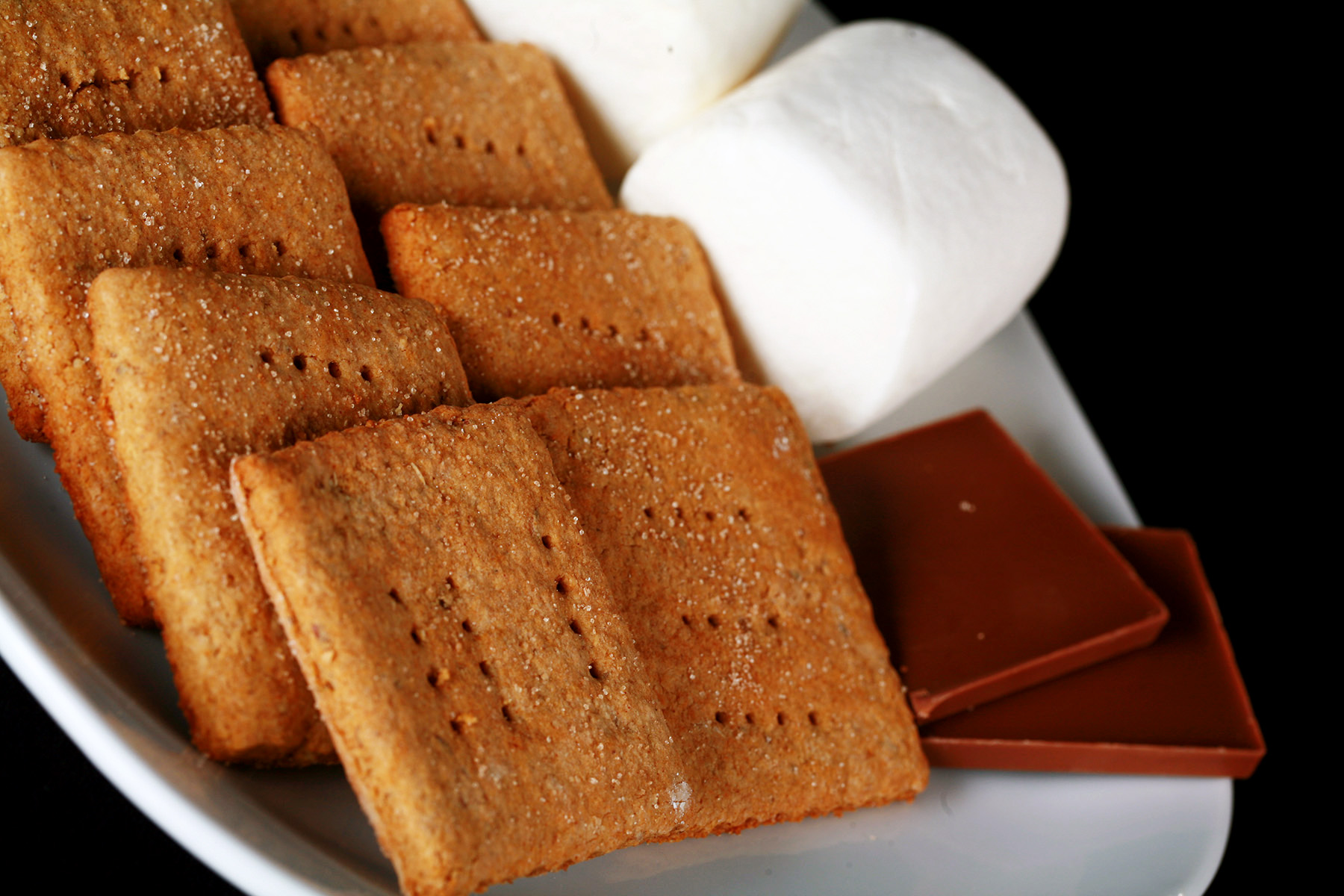 A white plate with rows of square shaped gluten-free graham crackers, a couple large marshmallows, and a piece of chocolate.