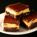 A plate of gluten-free Nanaimo Bars - A fudgey brownie, topped with a rich custard buttercream and a layer of chocolate ganache.