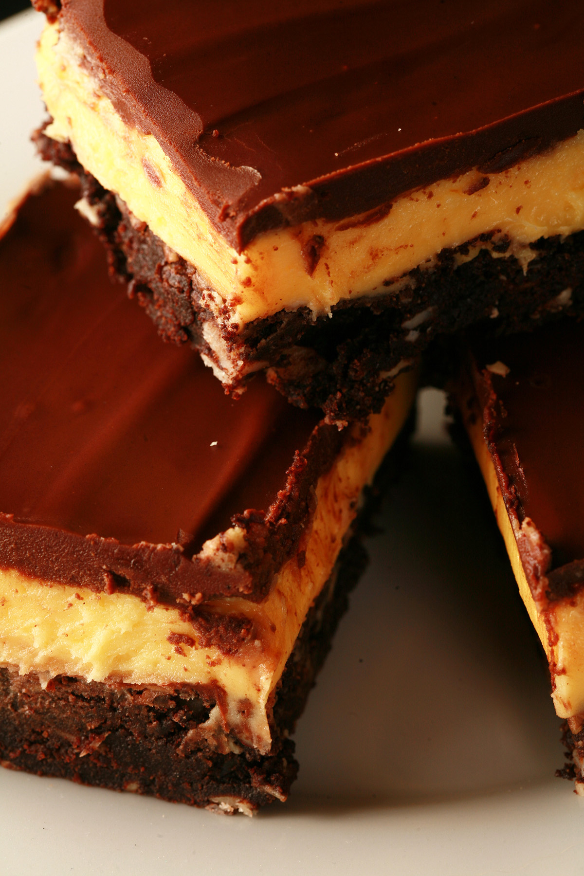 A plate of gluten-free Nanaimo Bar Brownies - A fudgey brownie, topped with a rich custard buttercream and a layer of chocolate ganache.
