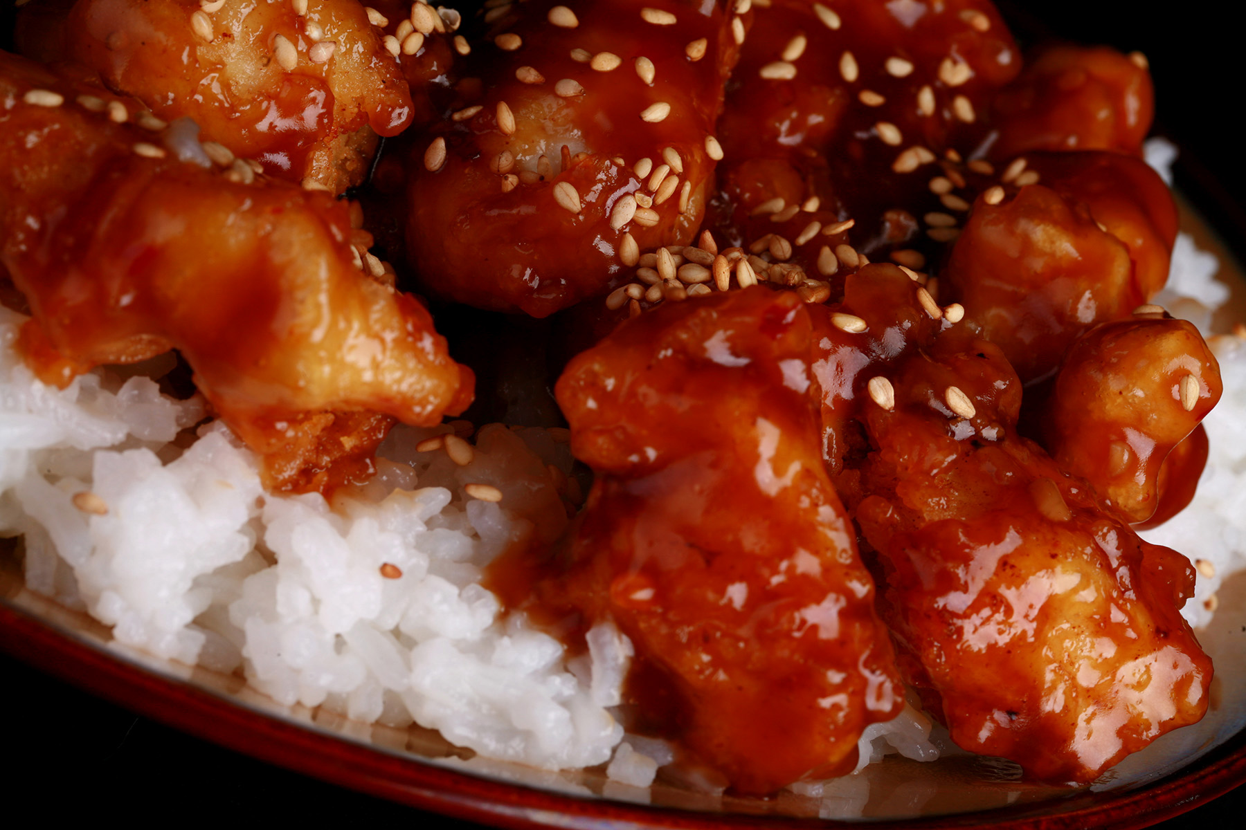 A close up view of a plate of white rice, topped with gluten-free sesame chicken. Chunks of battered and fried chicken in a glossy brown sauce, sprinkled with sesame seeds.
