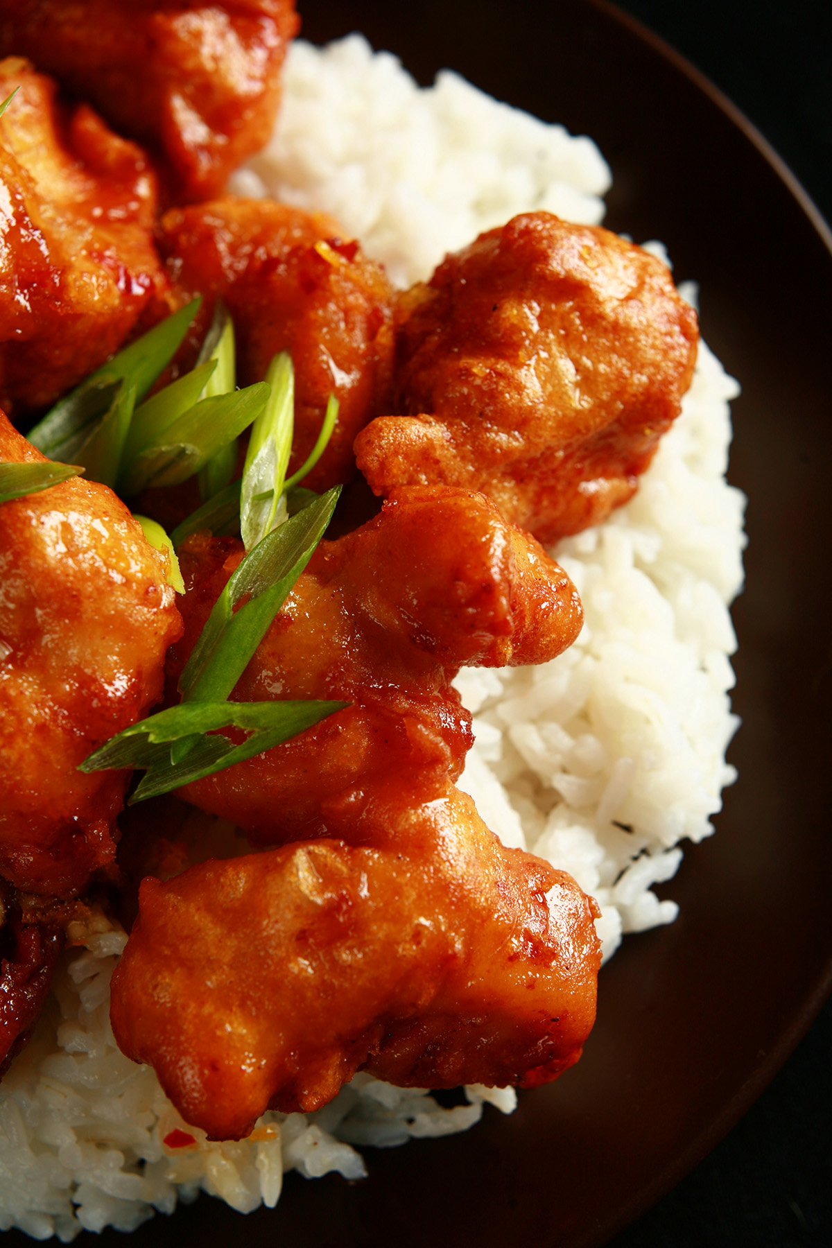 A plate of rice, covered with orange chicken: Chunks of battered and deep fried chicken coated in a glossy orange sauce, garnished with sliced green onions.