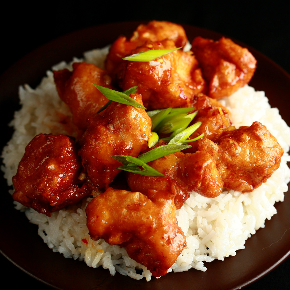 A plate of rice, covered with gluten-free orange chicken: Chunks of battered and deep fried chicken coated in a glossy orange sauce, garnished with sliced green onions
