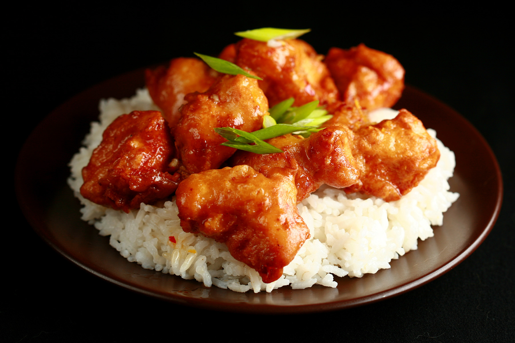A plate of rice, covered with gluten-free spicy orange chicken: Chunks of battered and deep fried chicken coated in a glossy orange sauce, garnished with sliced green onions.