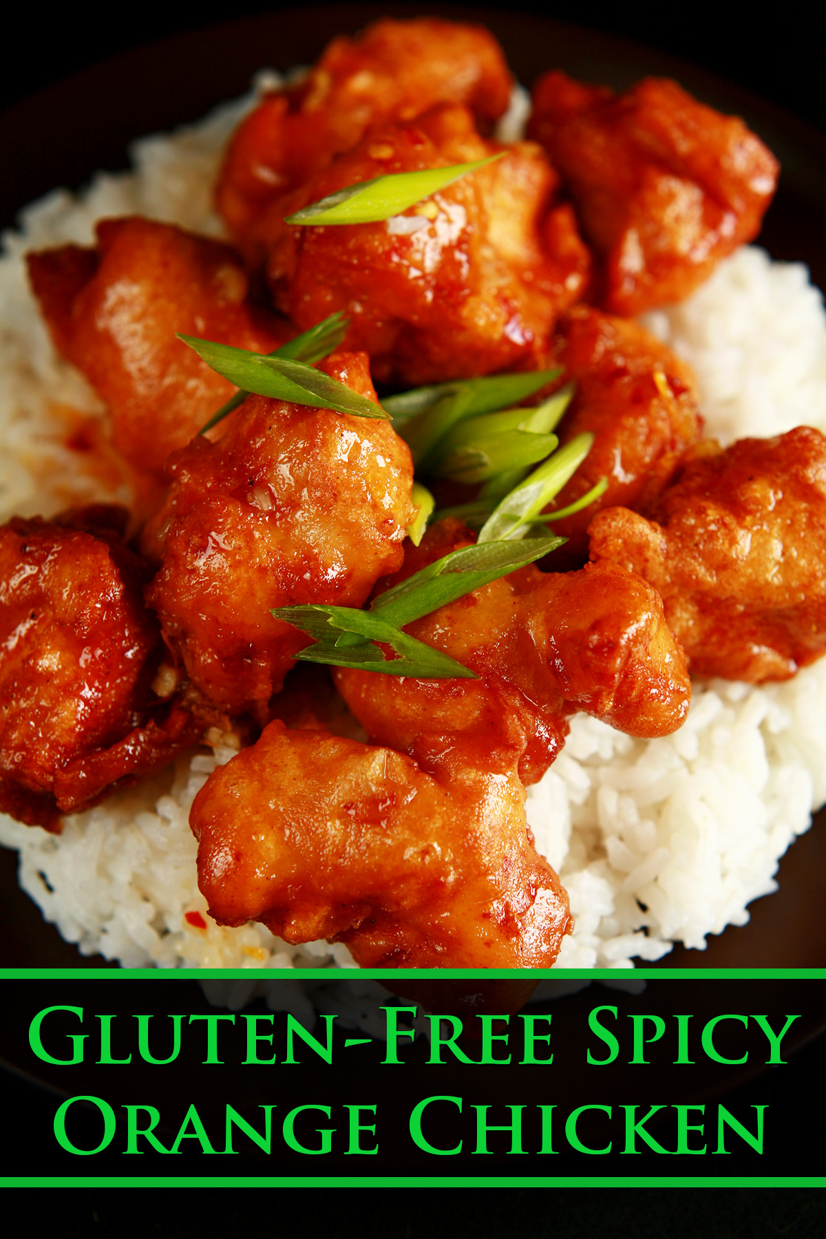 A plate of rice, covered with gluten-free orange chicken: Chunks of battered and deep fried chicken coated in a glossy orange sauce, garnished with sliced green onions.