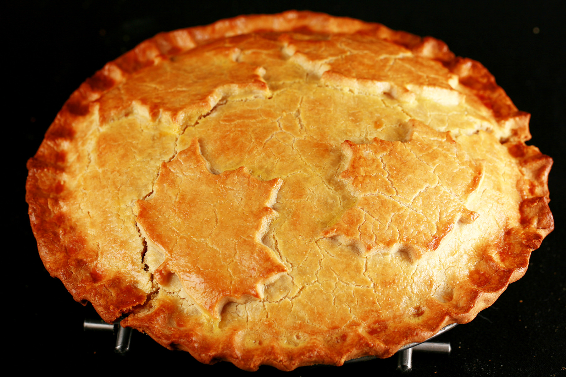 A golden brown gluten-free tourtiere meat pie, with a maple leaf design on top.