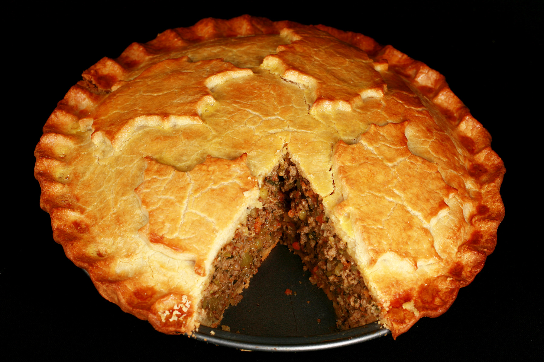 A golden brown gluten-free tourtiere meat pie, with a maple leaf design on top.. There is a section cut out of it