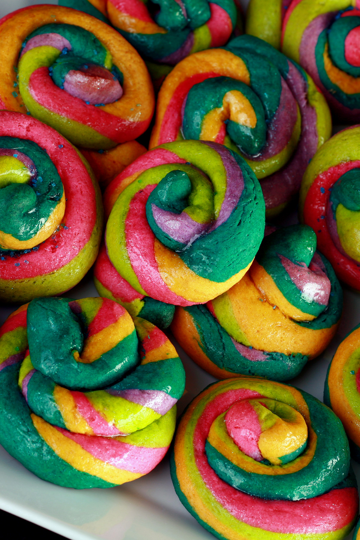 """A close up view of a pile of gluten-free unicorn poop cookies.  They are brightly coloured cookie """"poops"""" made from brightly coloured twists of cookie dough."""